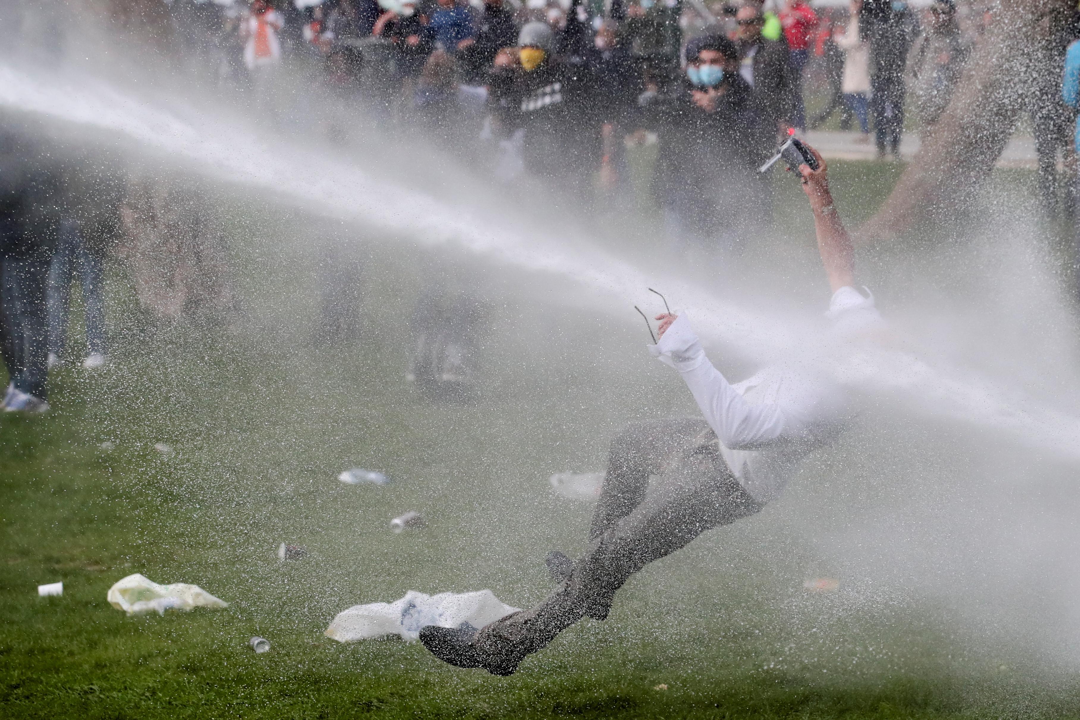 """在冲突中,当人们聚集在Bois de la Cambre / Ter Kamerenbos公园参加名为"""" La Boum 2""""的聚会时,一个人被水炮所淹没,这违反了比利时的冠状病毒病(COVID-19)社会疏远措施和限制。比利时布鲁塞尔,1年2021月XNUMX日。路透社/伊夫·赫尔曼(Yves Herman)"""