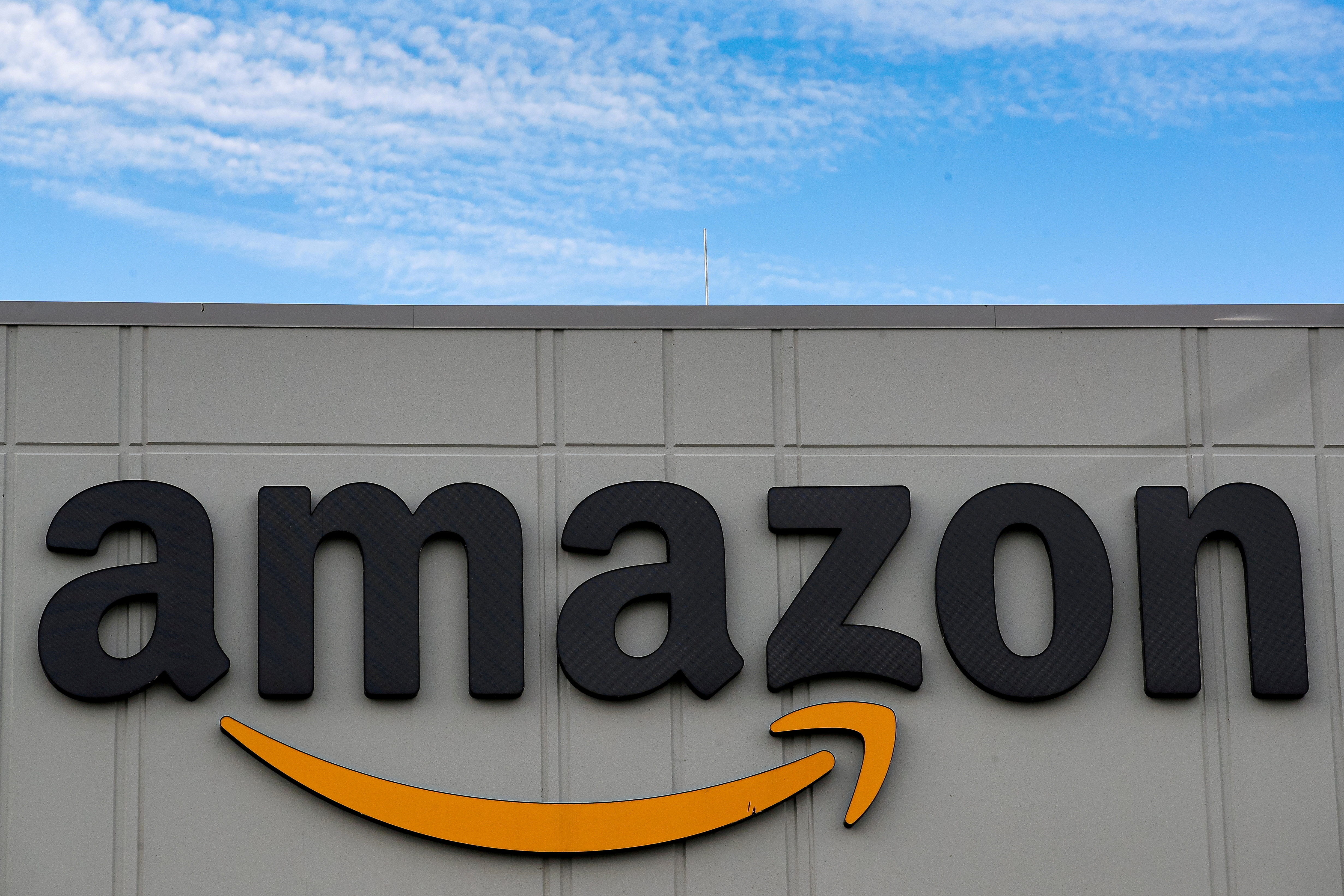 The Amazon logo is seen outside its JFK8 distribution center in Staten Island, New York, U.S. November 25, 2020.  REUTERS/Brendan McDermid.