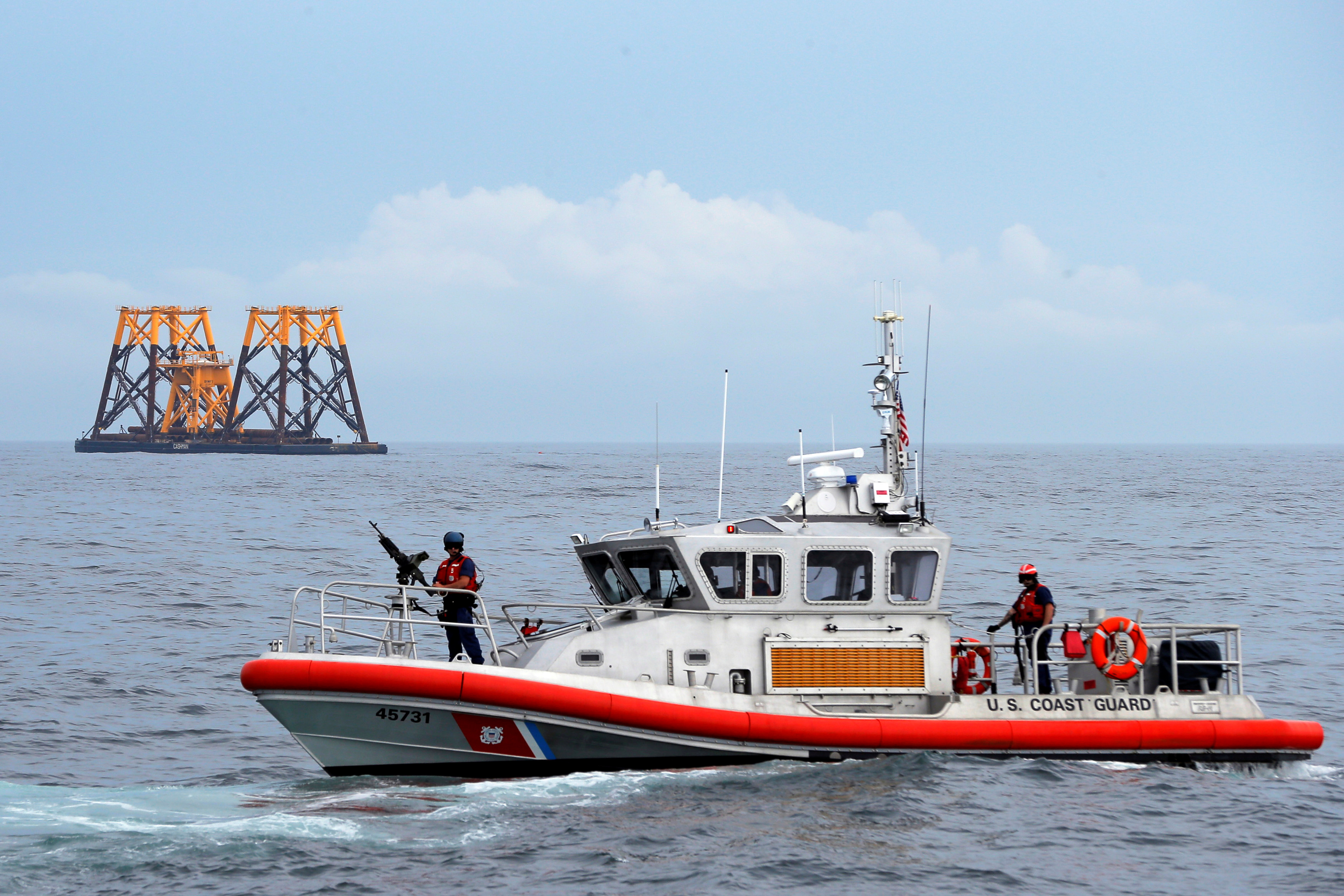 A U.S. Coast Guard patrol boat passes a barge carrying jacket supports and platforms for wind turbines in the waters of the Atlantic Ocean off Block Island, Rhode Island July 27, 2015.       REUTERS/Brian Snyder/File Photo