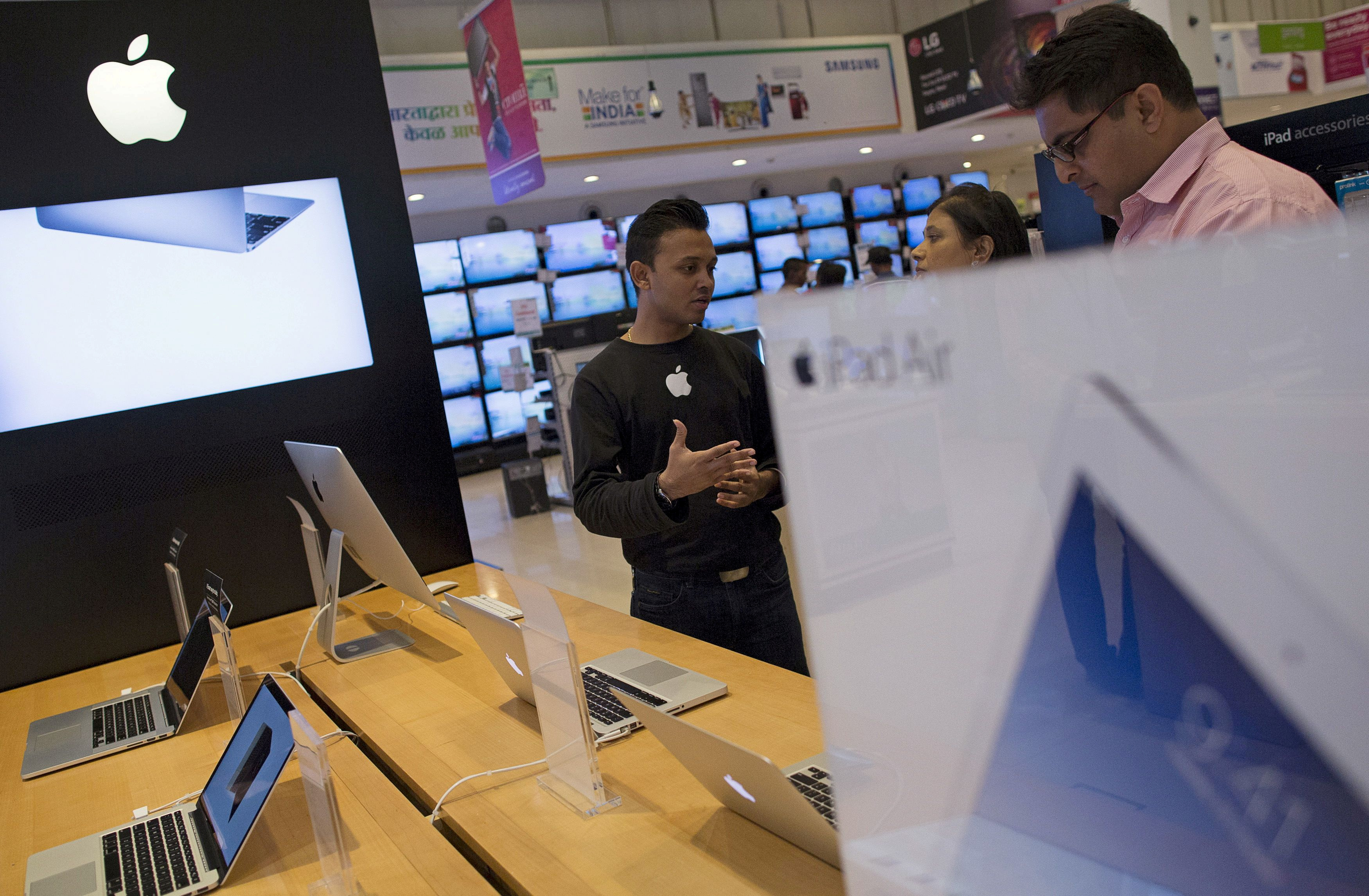 An Apple salesperson speaks to customers at an electronics store in Mumbai, India, July 23, 2015. REUTERS/Danish Siddiqui/File Photo