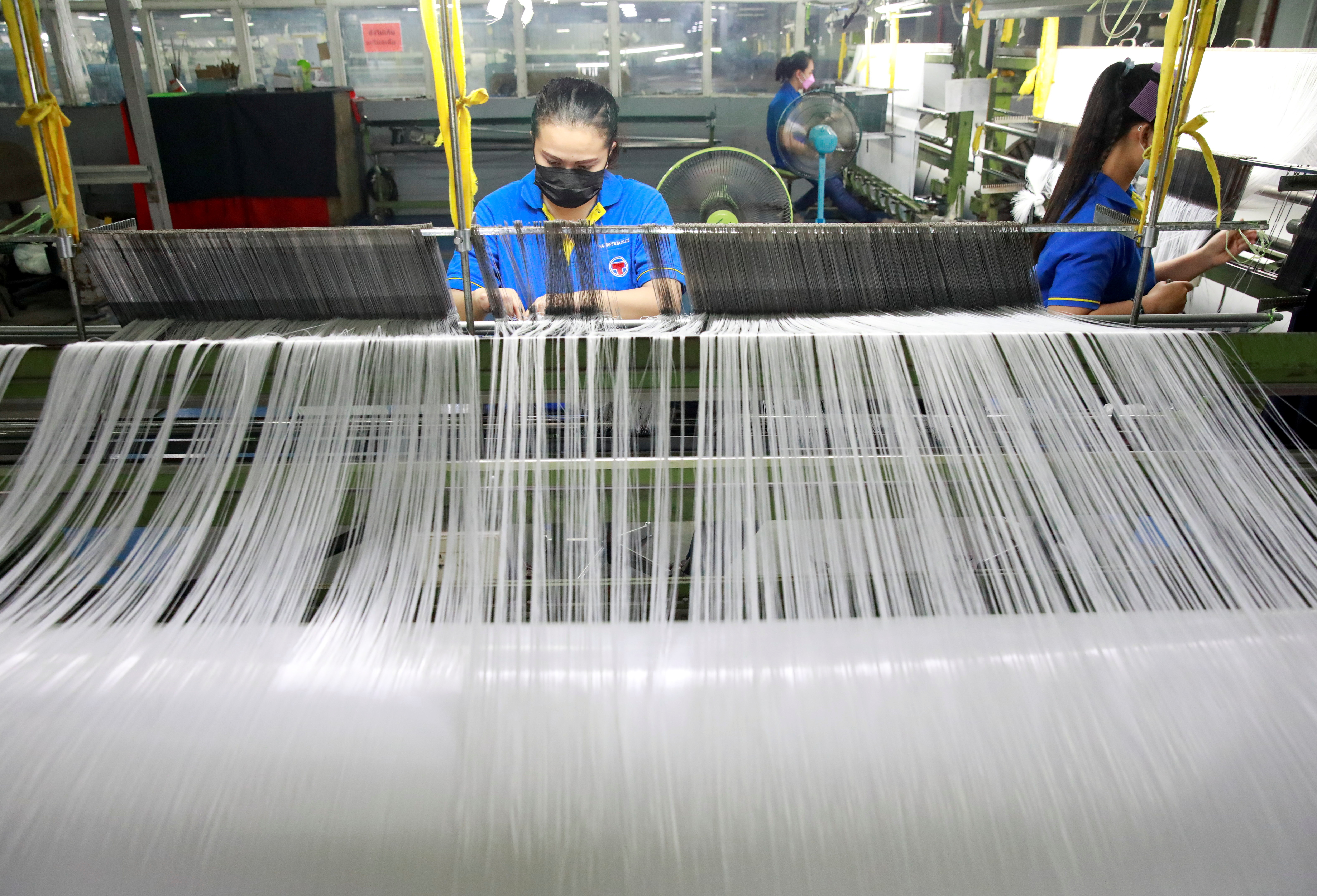Women work in a weaving factory, as Bangkok city administration and temples drive efforts to encourage the public to donate plastic bottles, which will be collected and upcycled into reusable Personal Protective Equipment (PPE) to reduce plastic waste as Thailand battles coronavirus disease (COVID-19) pandemic, in Bangkok, Thailand September 1, 2021. Picture taken September 1, 2021. REUTERS/Soe Zeya Tun