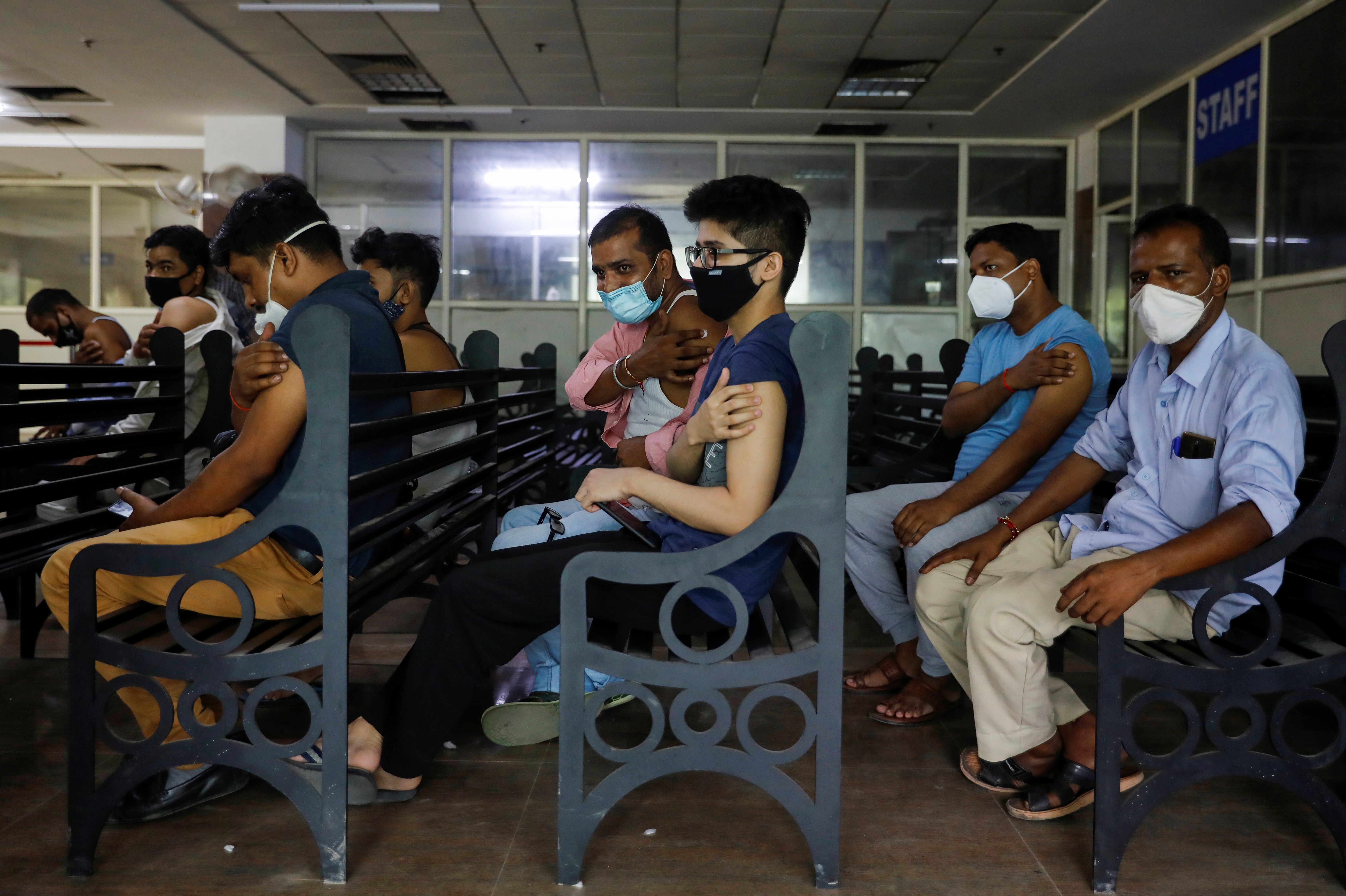 People wait at the observation area after receiving a dose of COVISHIELD, a vaccine against coronavirus disease (COVID-19) manufactured by Serum Institute of India, at a hospital in Noida on the outskirts of New Delhi, India, August 30, 2021. REUTERS/Adnan Abidi