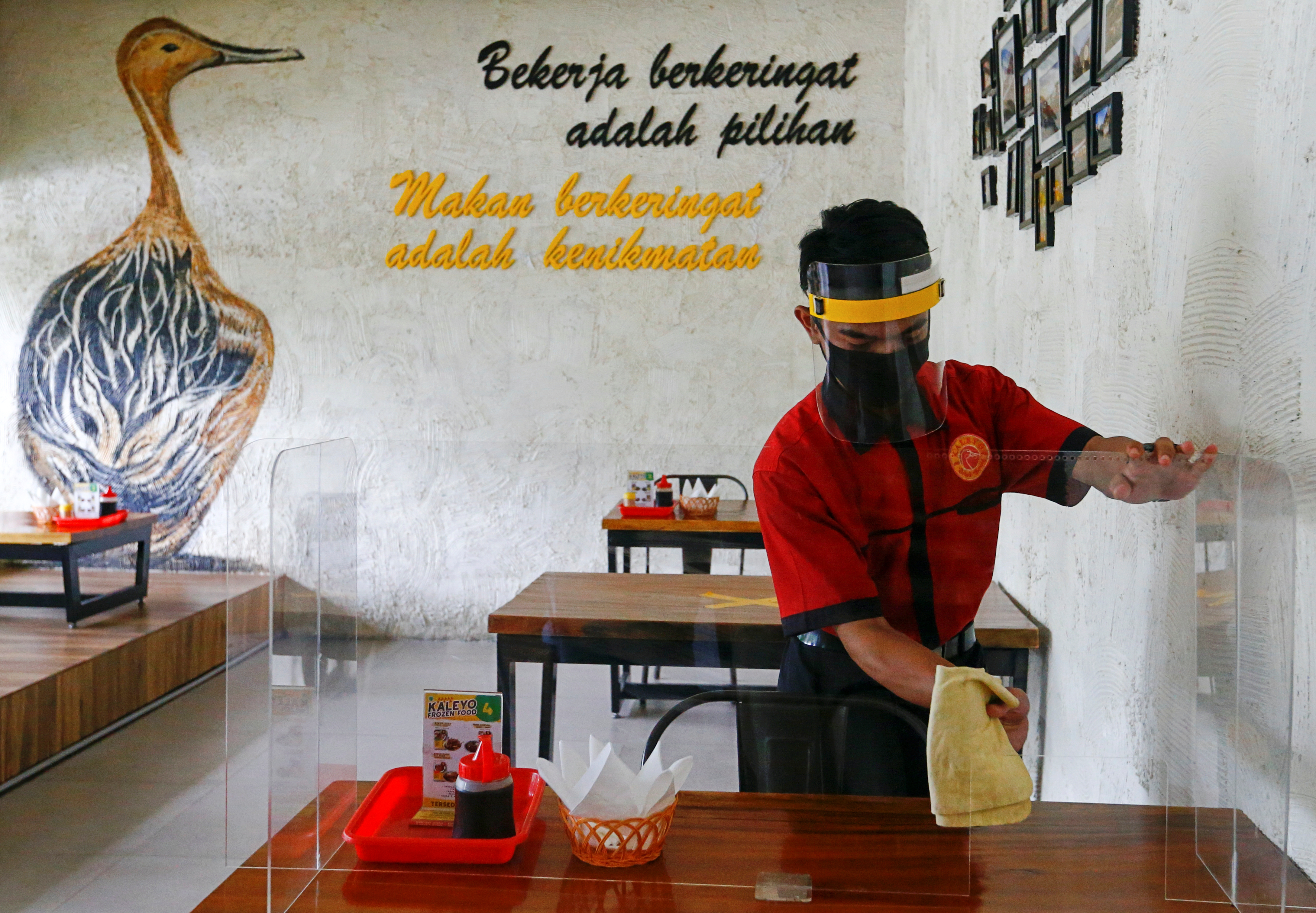 A worker wearing a face shield and a mask wipes a protective screen on a table at a restaurant, as the Indonesian capital kicks off a two-week