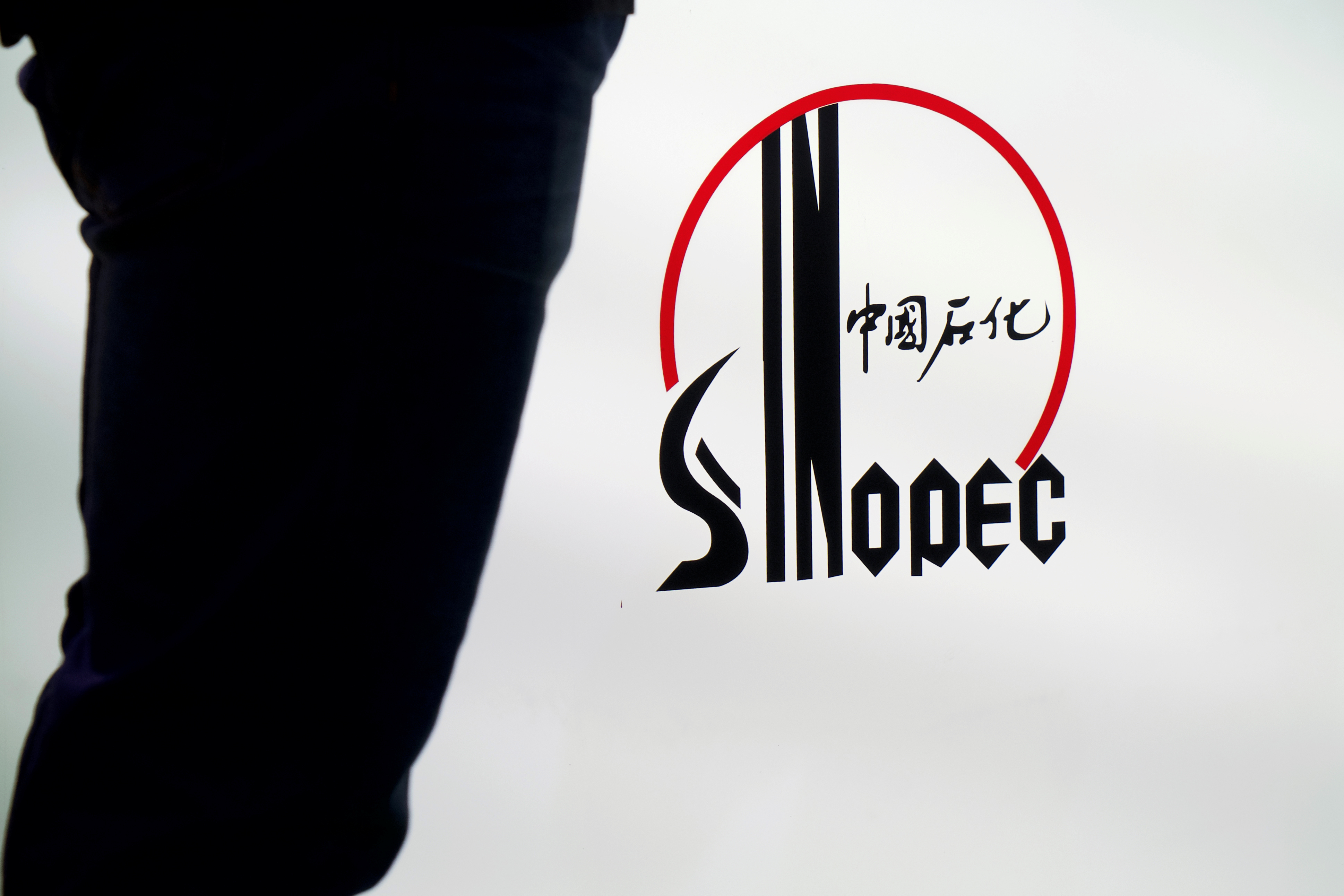 A man stands next to a logo of Sinopec, or China Petroleum and Chemical Corporation, at an expo on rubber technology in Shanghai, China September 19, 2018. Picture taken September 19, 2018. REUTERS/Stringer