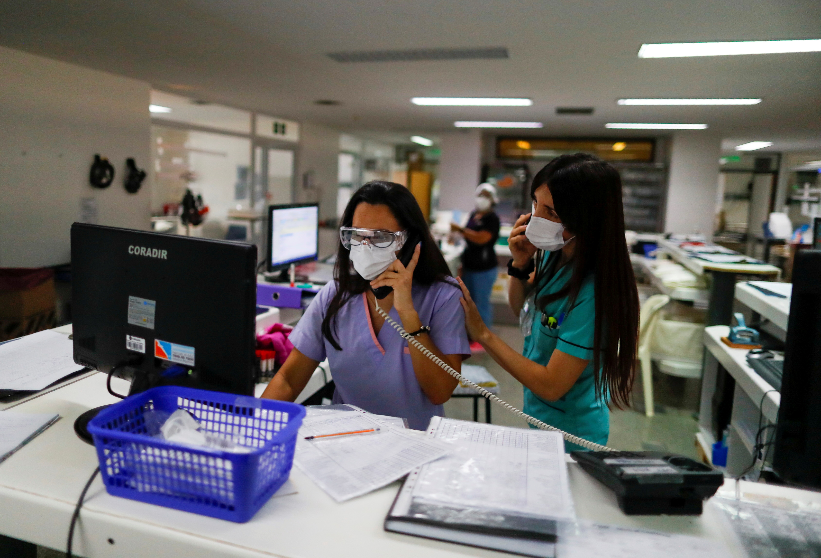 Healthcare workers speak on the phone at an intensive care unit of a hospital prepared for patients suffering from the coronavirus disease (COVID-19), on the outskirts of Buenos Aires, Argentina April 16, 2021. REUTERS/Agustin Marcarian/
