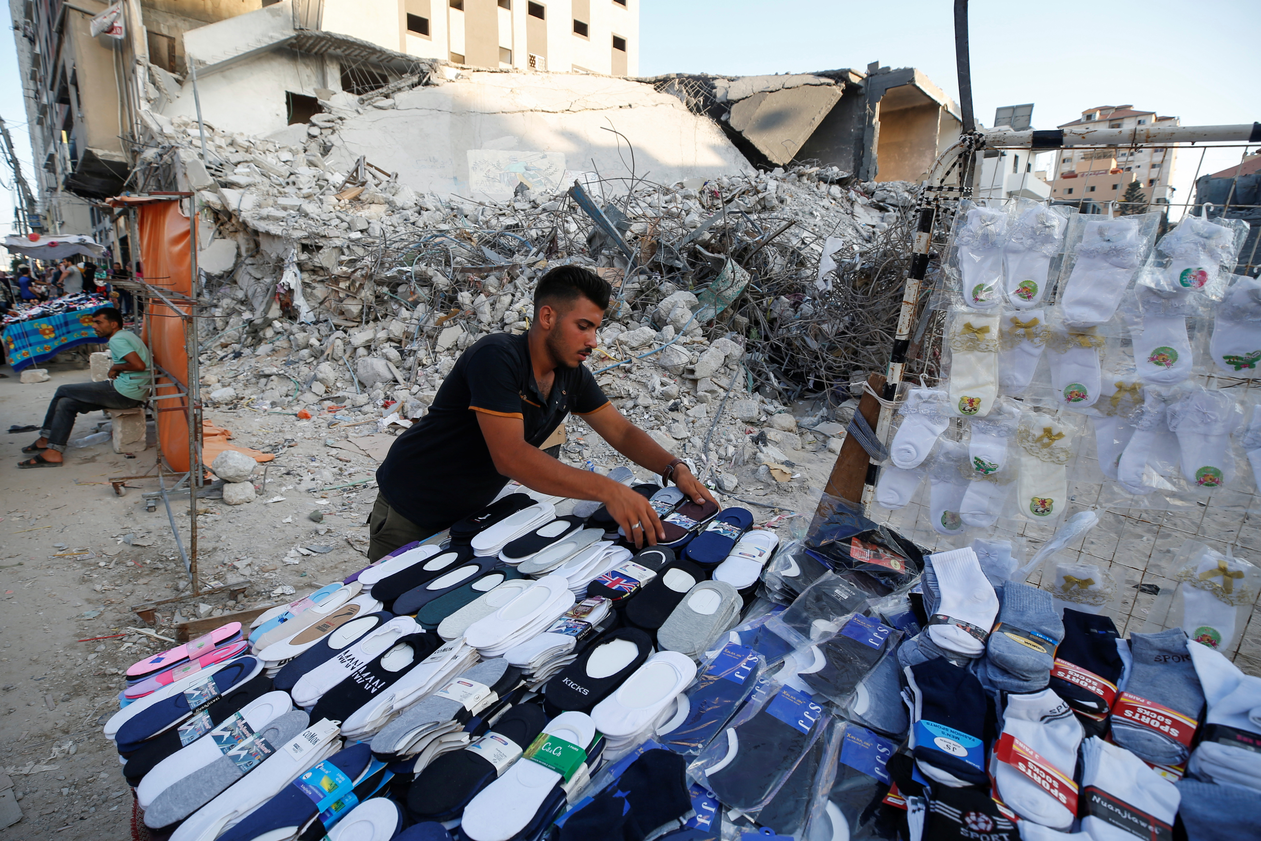 A Palestinian sells socks on a stall near the rubble of his old store that has been destroyed in an Israeli air strike, ahead of Eid Al-Adha Muslim holiday, in Gaza City, July 14, 2021. Picture taken July 14, 2021. REUTERS/Mohammed Salem