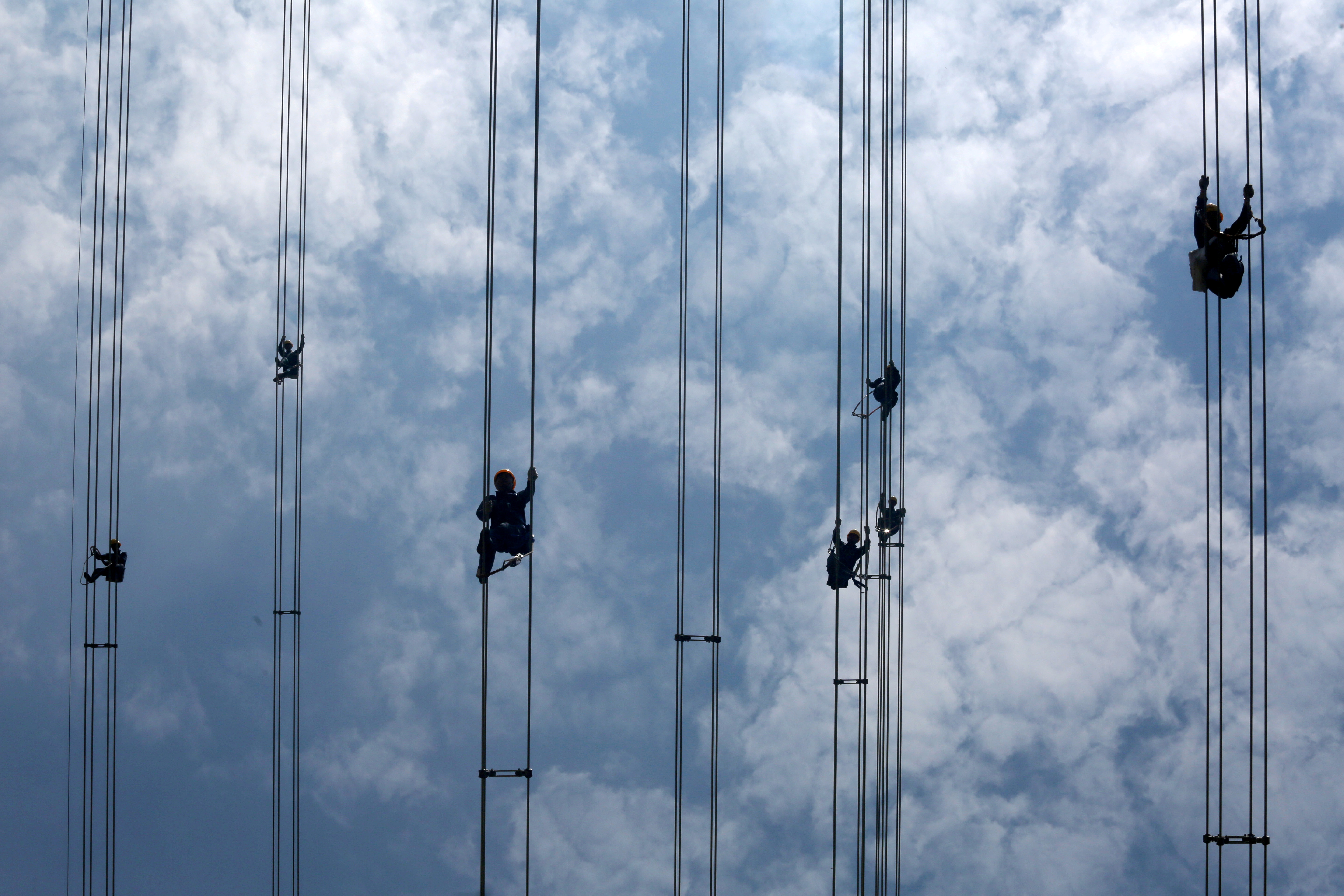 Workers of grid operator China Southern Power Grid inspect power cables connecting transmission towers in Dongguan, Guangdong province, China May 29, 2018. Picture taken May 29, 2018. REUTERS/Stringer