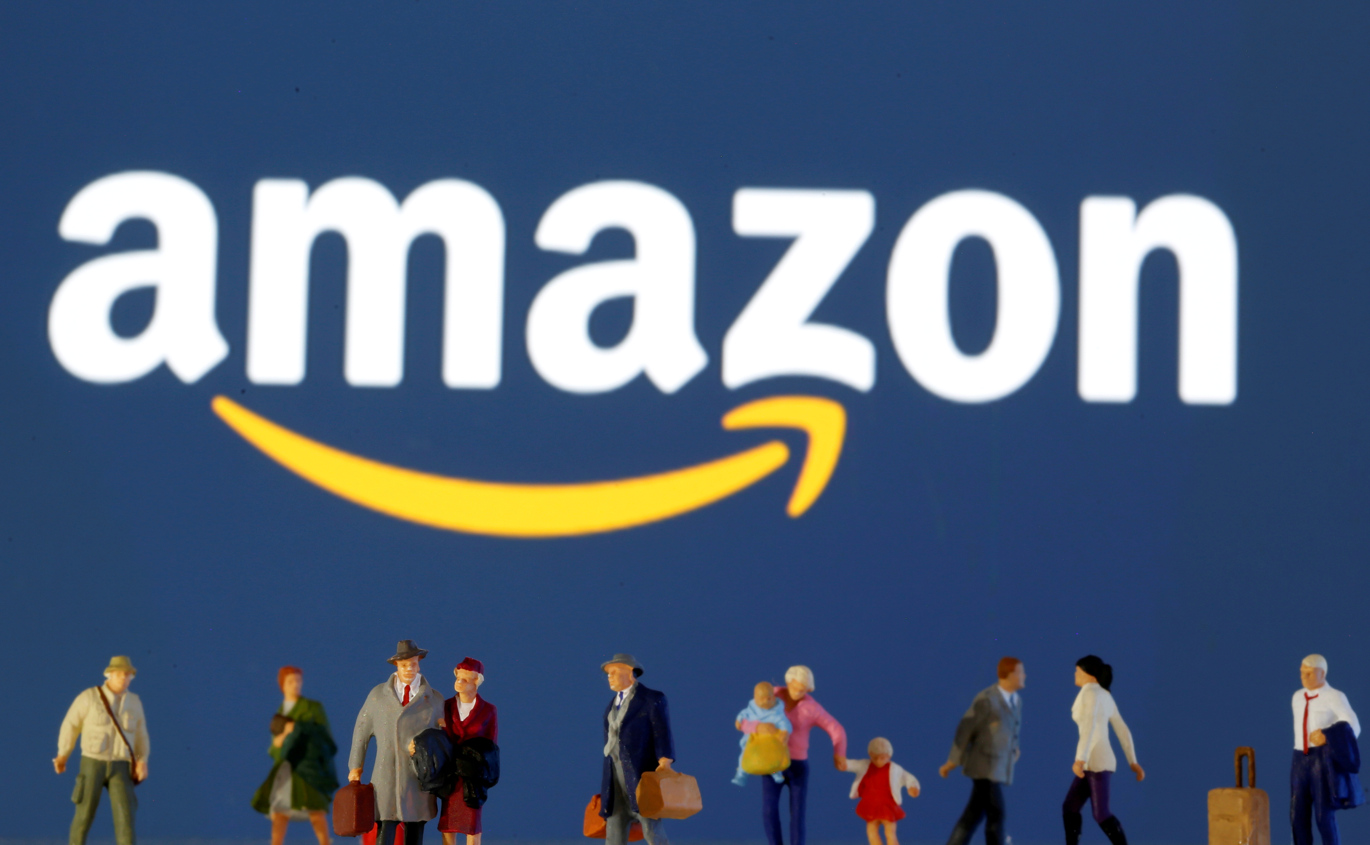 Small toy figures are seen in front of diplayed Amazon logo, March 19, 2020. REUTERS/Dado Ruvic/Illustration