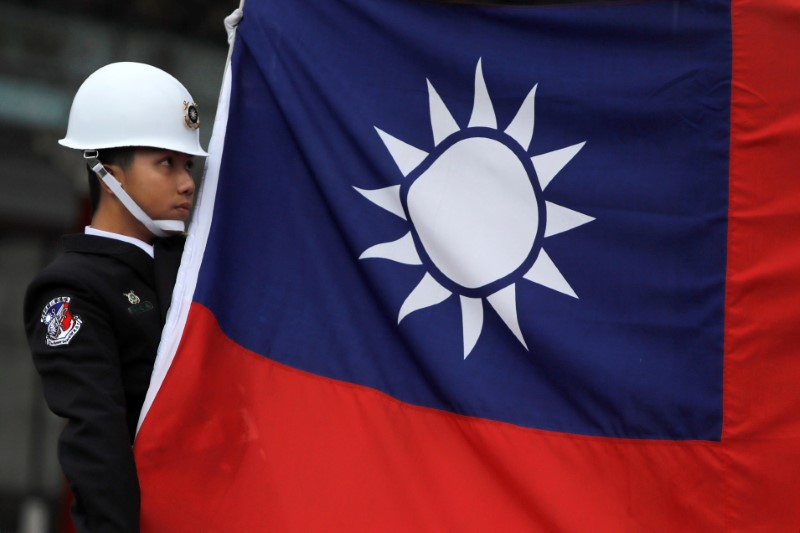 A military honour guard holds a Taiwanese national flag as he attending flag-raising ceremony at Chiang Kai-shek Memorial Hall, in Taipei, Taiwan March 16, 2018. REUTERS/Tyrone Siu/File Photo