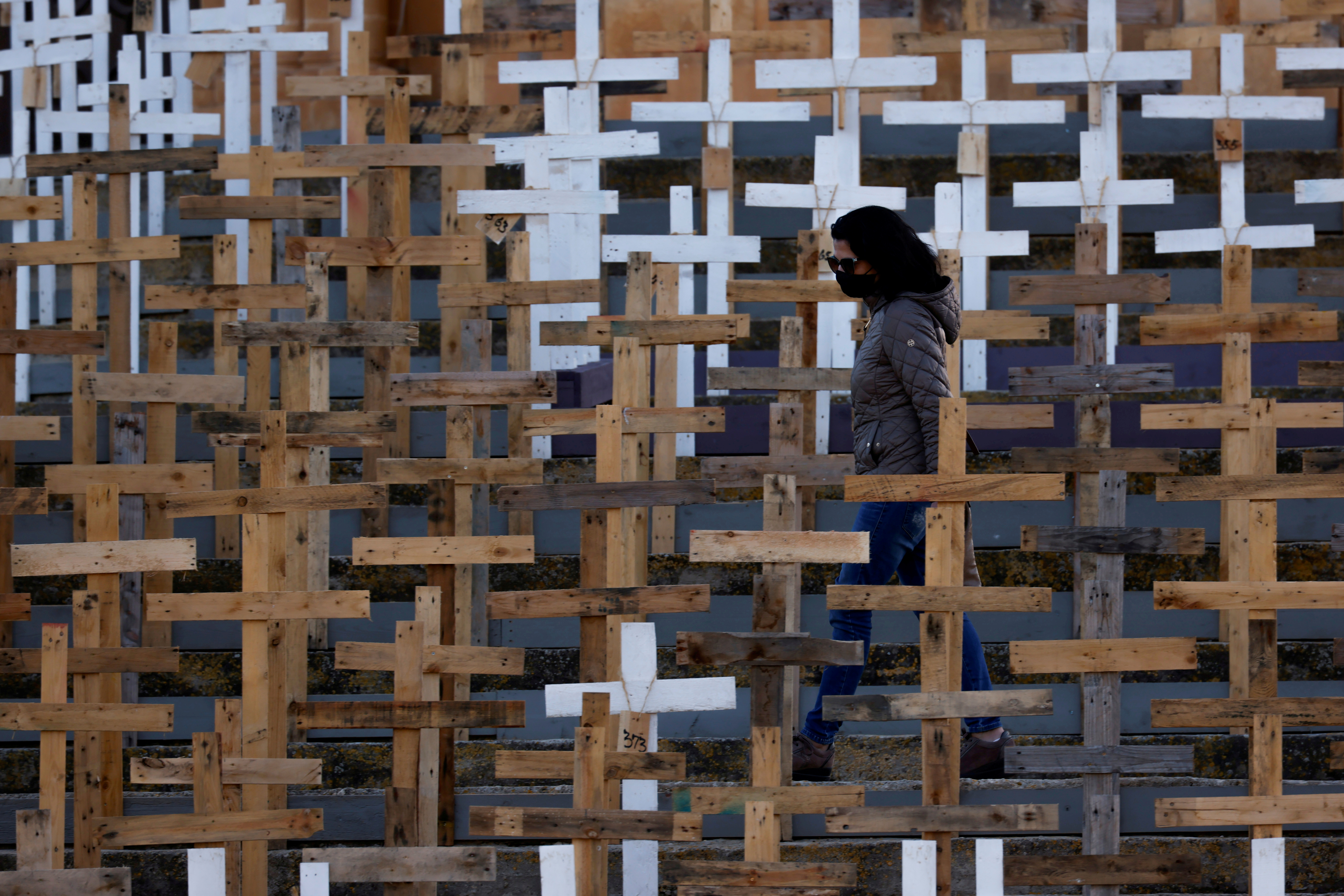 A woman wearing a mask walks among hundreds of crosses set up in front of the Parish Church of Our Lady of Loreto to commemorate Holy Week and as a memorial to the victims of the coronavirus disease (COVID-19) pandemic, in the village of Ghajnsielem on the island of Gozo, Malta March 27, 2021. REUTERS/Darrin Zammit Lupi