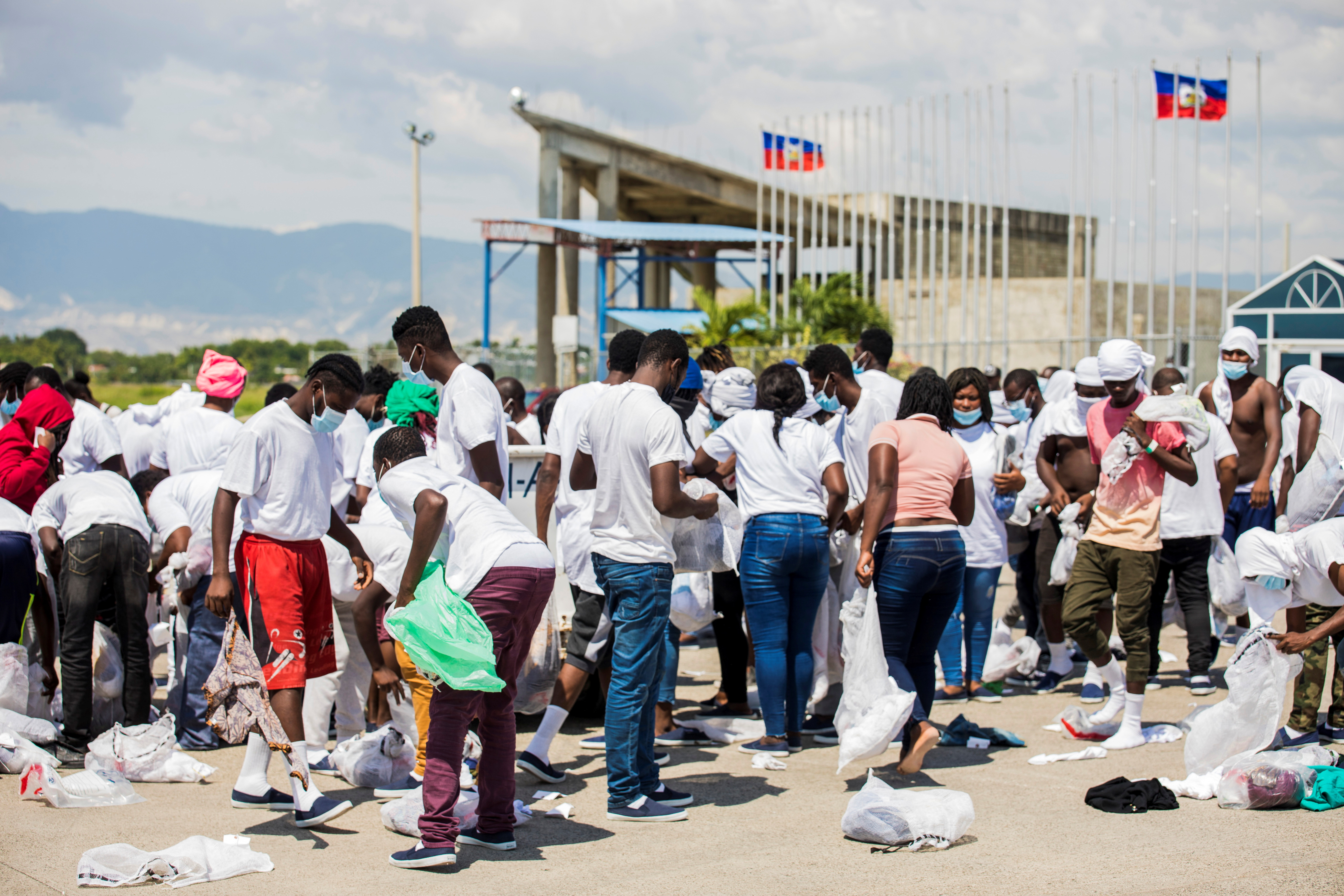 Haitian migrants collect their belongings after U.S. authorities flew them out of a Texas border city after crossing the Rio Grande river from Mexico, at Toussaint Louverture International Airport in Port-au-Prince, Haiti September 21, 2021. REUTERS/Ralph Tedy Erol