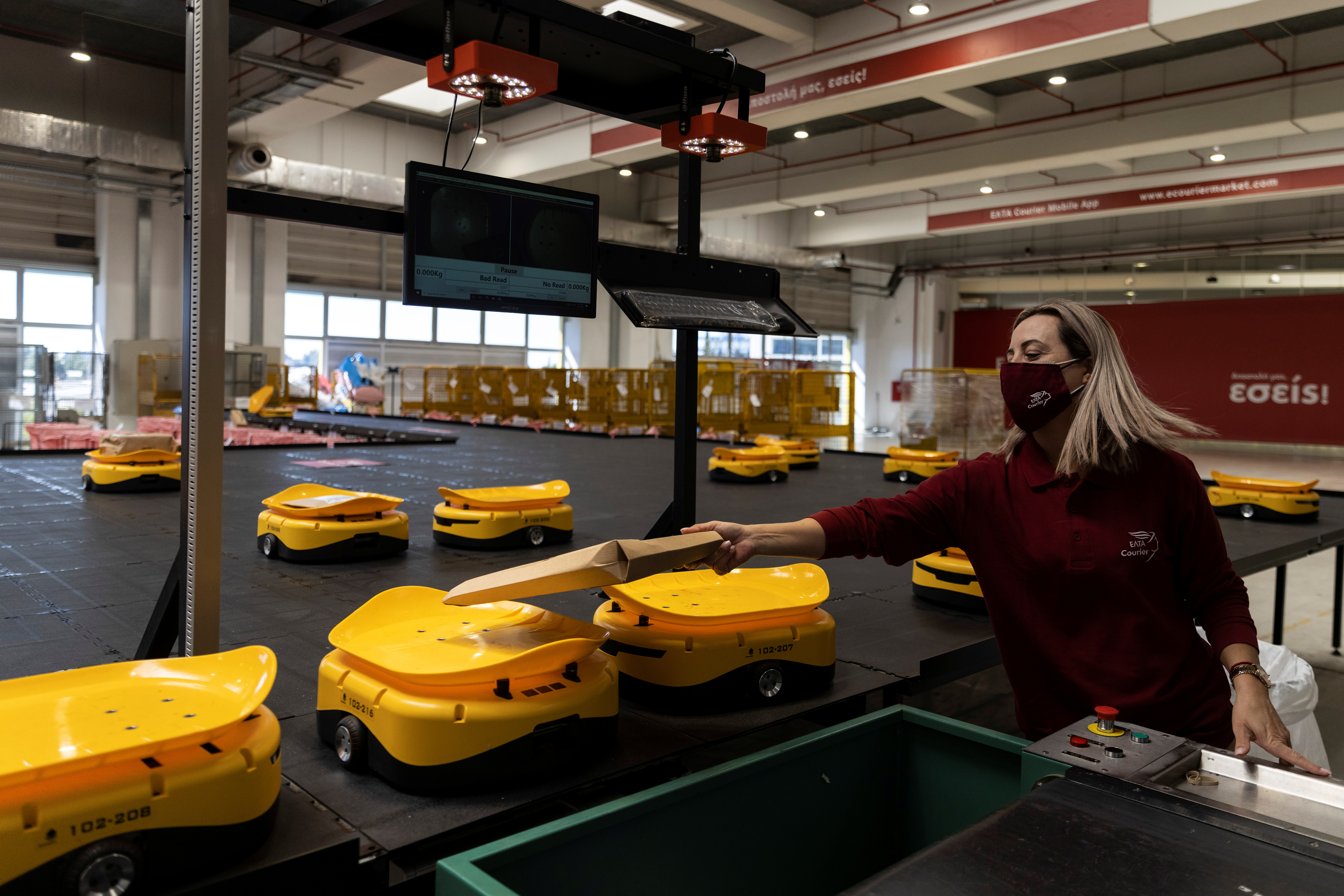 An employee places a parcel on a robot at the Hellenic Post's sorting centre in Kryoneri, Greece, October 4, 2021. Picture taken October 4, 2021. REUTERS/Alkis Konstantinidis