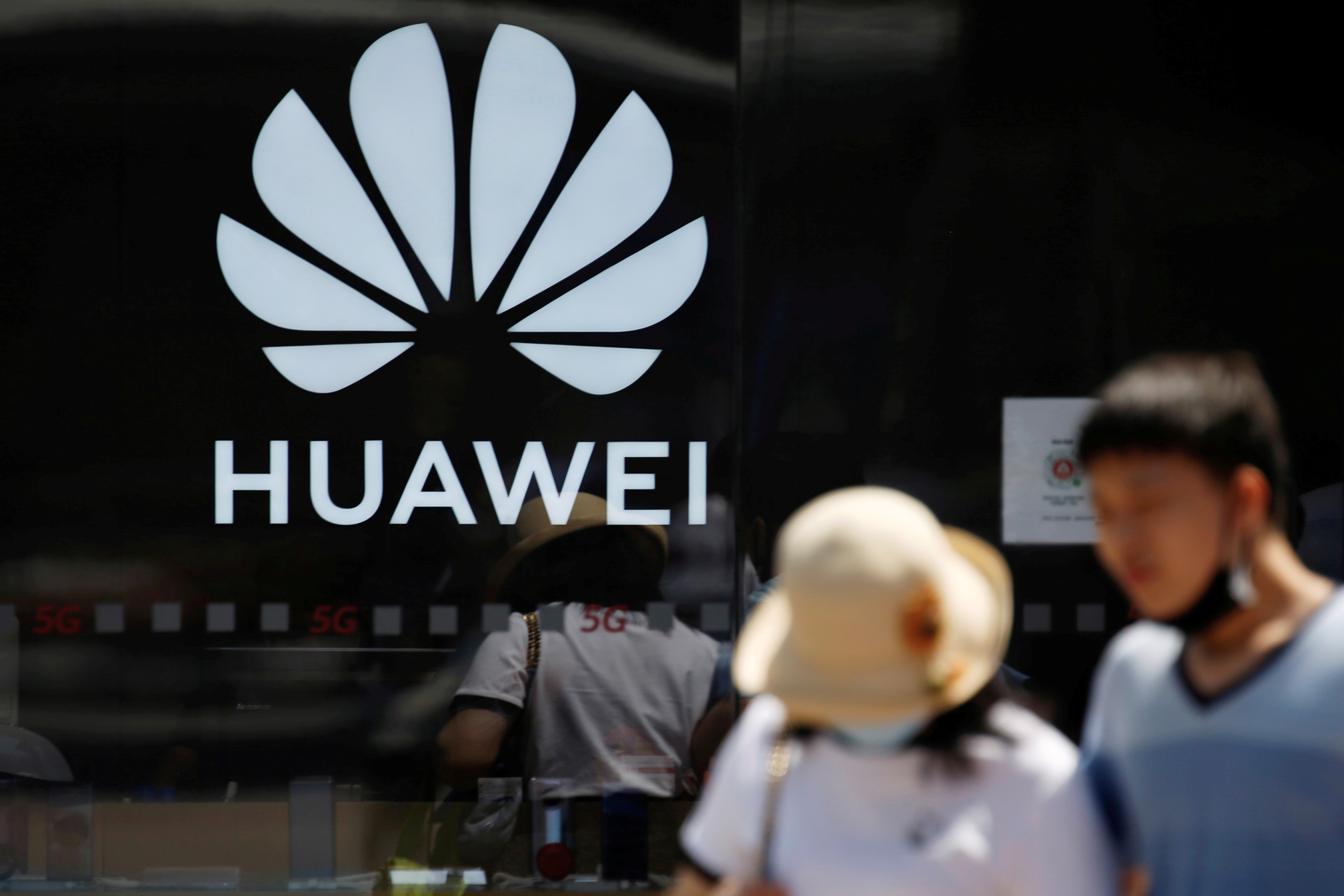 People walk past a Huawei logo on the facade of its store at a shopping complex in Beijing, China July 14, 2020. REUTERS/Tingshu Wang/File Photo