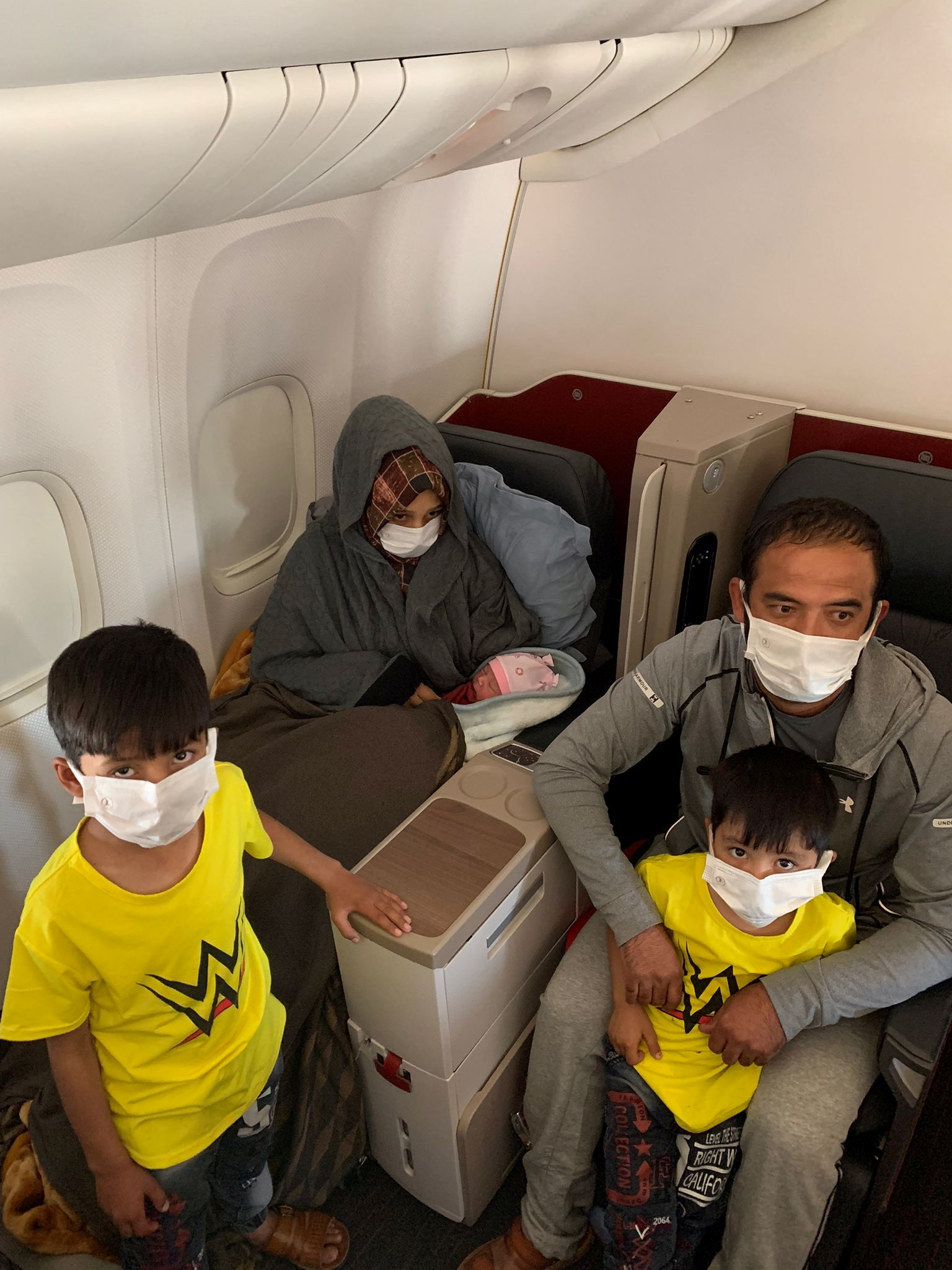 Afghan evacuee Soman Noori, accompanied by her husband Taj Moh Hammat and their sons, holds her newborn baby girl named Havva on board an evacuation flight operated by Turkish Airlines from Dubai to Britain's Birmingham, August 28, 2021. Turkish Airlines/Handout via REUTERS