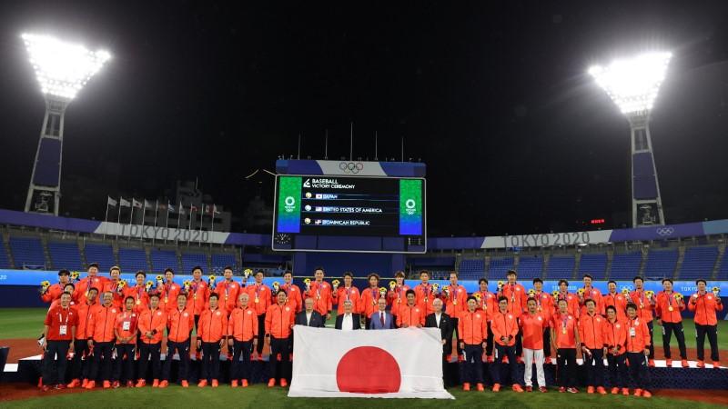Tokyo 2020 Olympics - Baseball - Men's Team - Medal Ceremony - Yokohama Baseball Stadium, Yokohama, Japan - August 7, 2021. Gold Medallists Japan celebrate on the podium with the flag of Japan. REUTERS/Jorge Silva