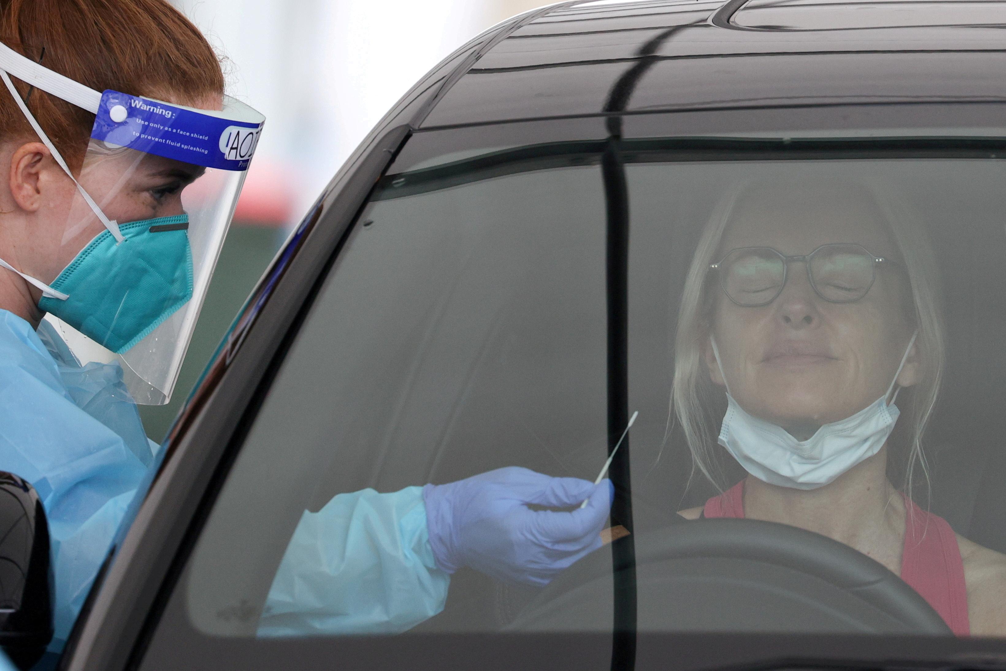A medical worker swabs a member of the public at the Bondi Beach drive-through coronavirus disease (COVID-19) testing centre as the city experiences an outbreak in Sydney, Australia, December 21, 2020. REUTERS/Loren Elliott