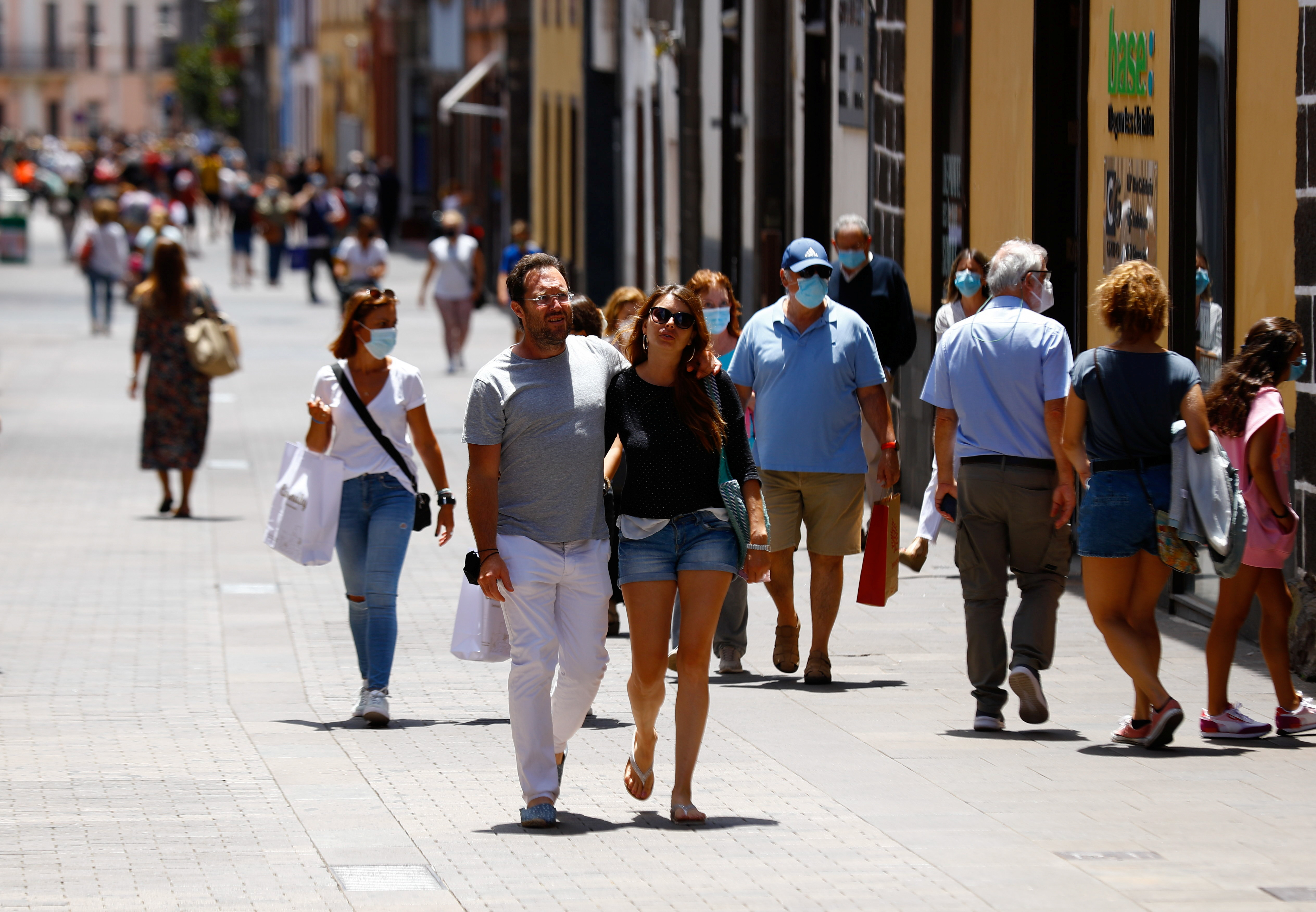 Two tourists walk without face masks in La Laguna on the day the Canary Islands government imposed stricter rules to control a surge in coronavirus disease (COVID-19) cases, on the island of Tenerife, Spain, July 26, 2021. REUTERS/Borja Suarez