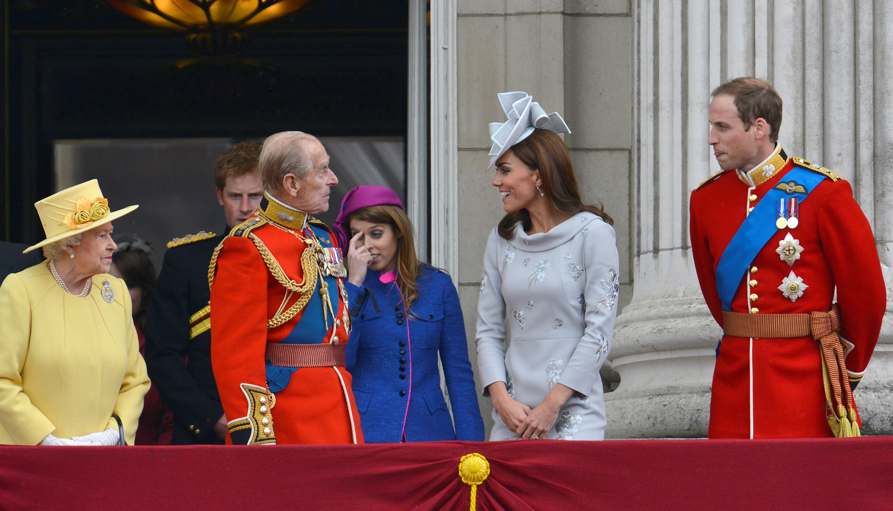 Britain's Queen Elizabeth (L) looks on as her husband Prince Philip, The Duke of Edinburgh, (4R) speaks with Prince William (R) and Catherine, Duchess of Cambridge (2nd R) with Prince Harry (5th R) and Princess Beatrice (3rd R) on the balcony of Buckingham Palace following the Trooping the Colour ceremony in central London June 16, 2012.   REUTERS/Toby Melville/File Photo