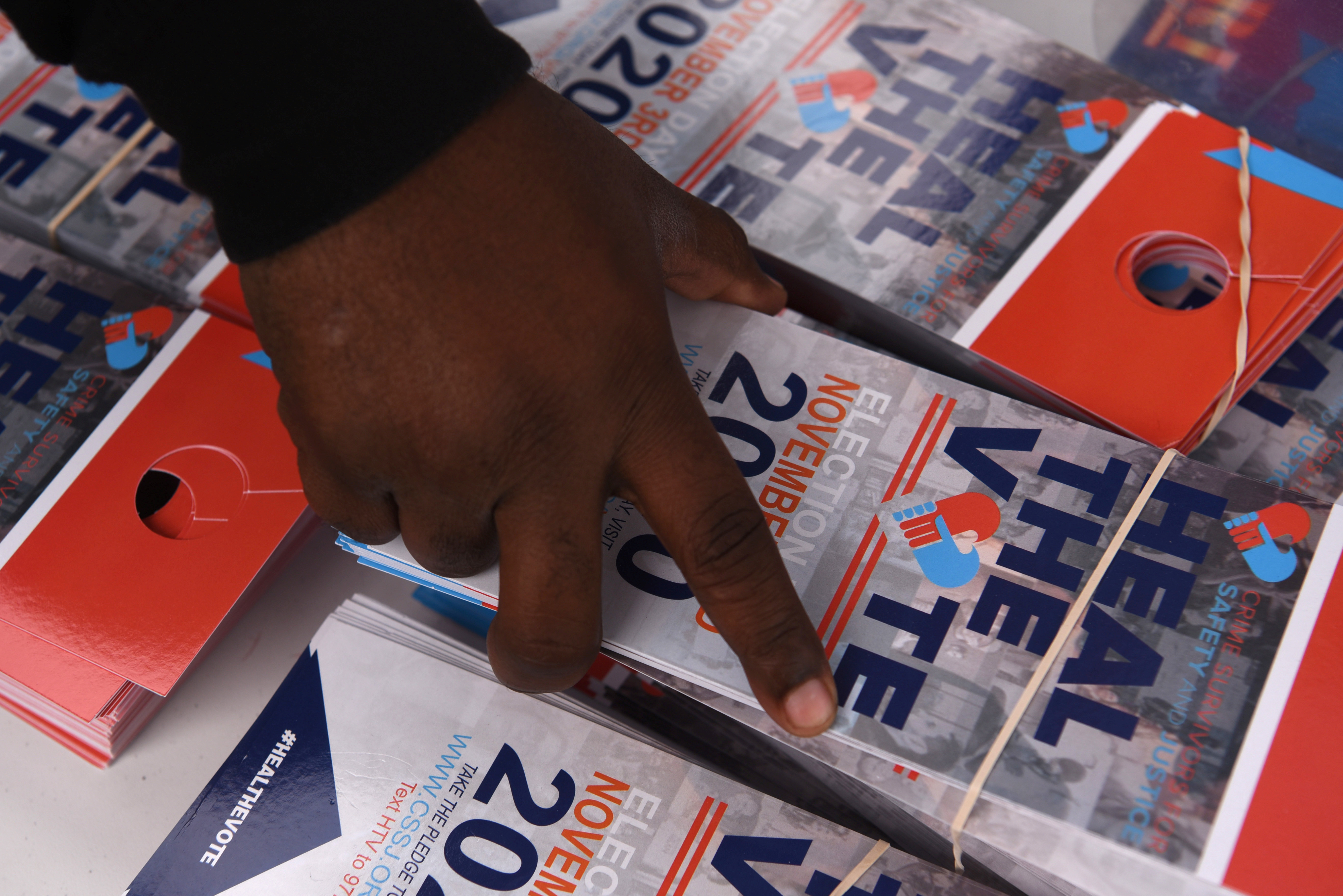 A man grabs flyers to hang on doorhandles at an event hosted by the NAACP to encourage community members to vote in the upcoming presidential election in Houston, Texas, U.S., October 24, 2020. Picture taken October 24, 2020.   REUTERS/Callaghan O'Hare