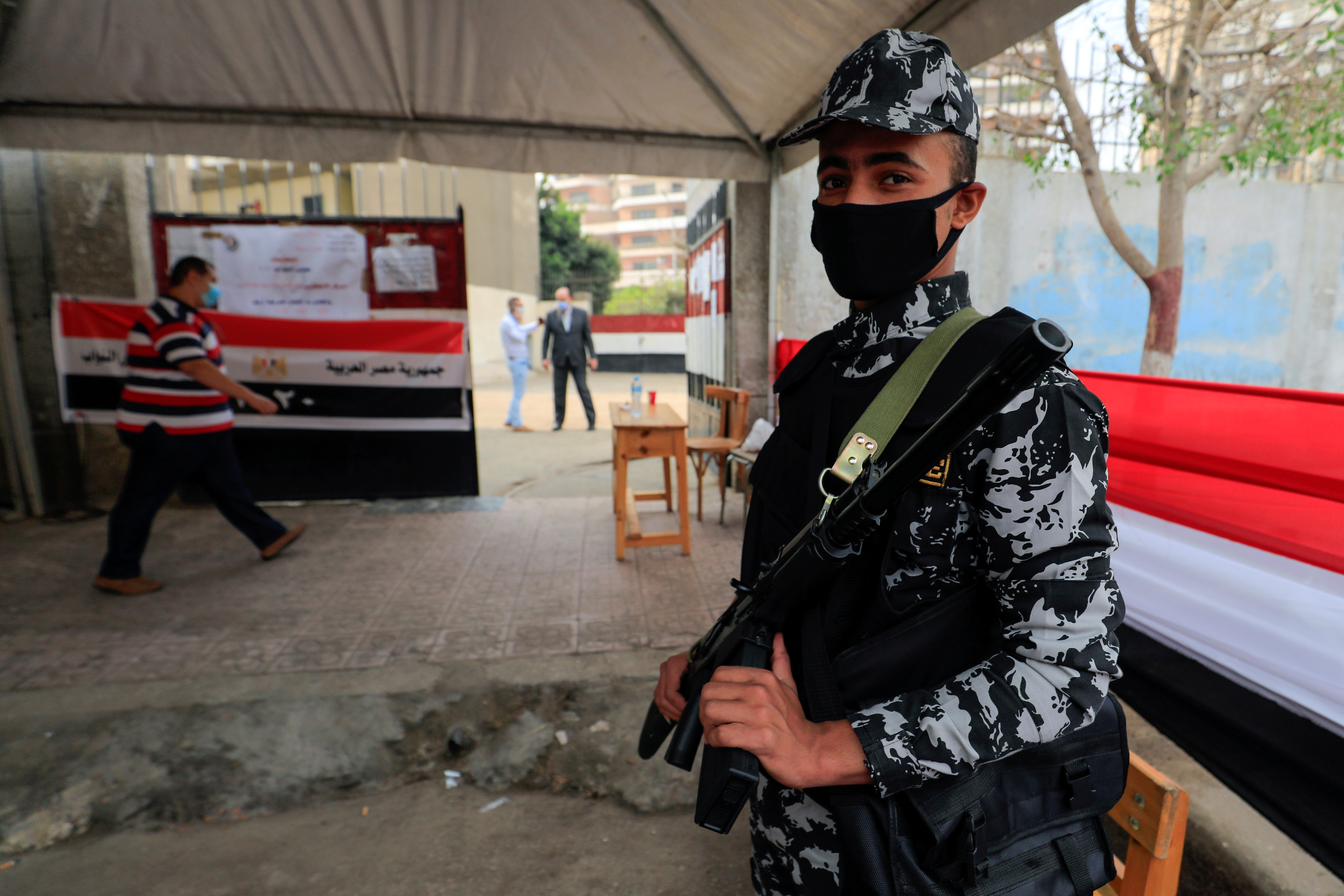 A security force member stands guard while people arrive to cast their vote, outside a school used as a polling station during the second round of Egypt's parliamentary election in Cairo, Egypt, November 7, 2020. REUTERS/Amr Abdallah Dalsh/File Photo
