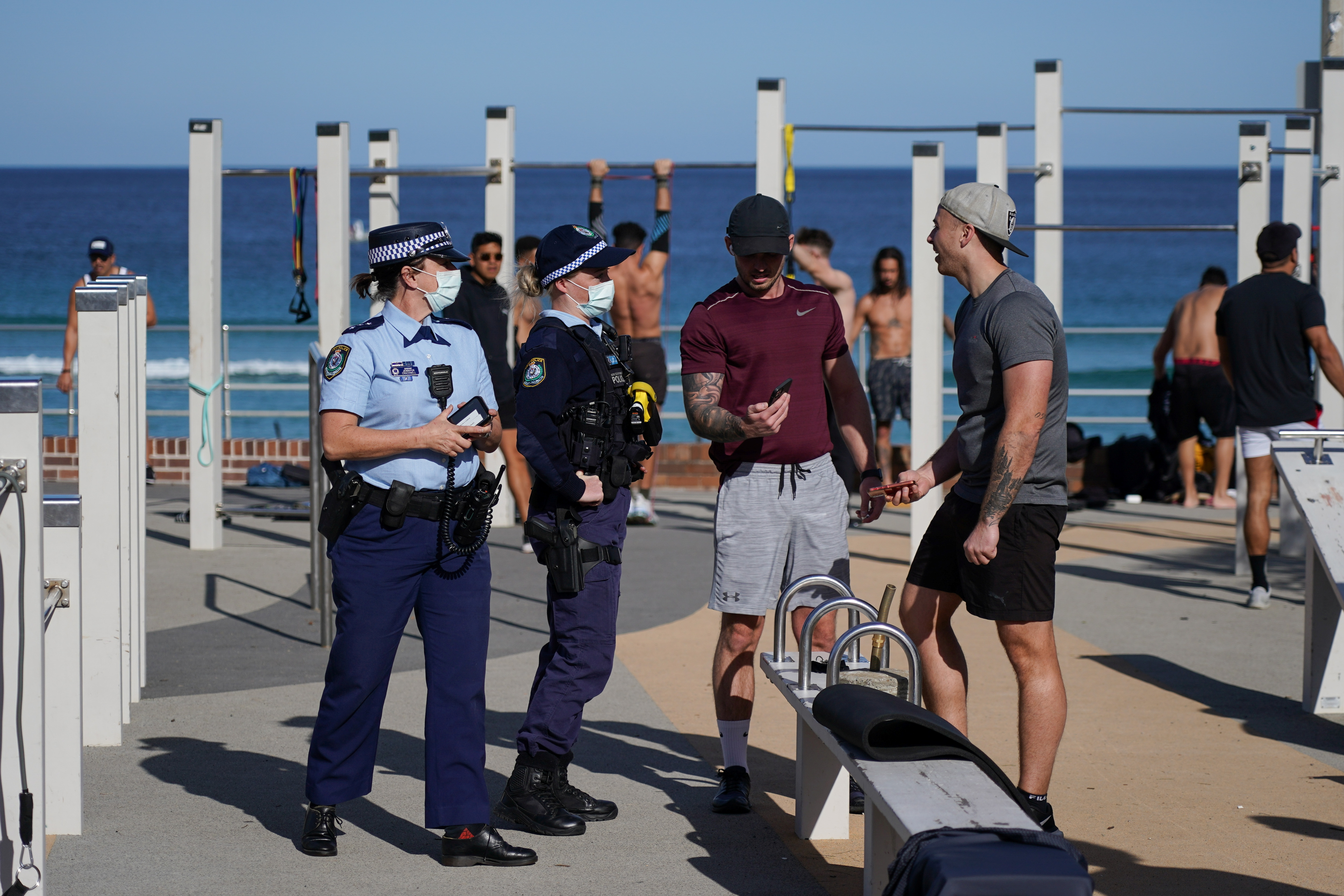 Patrolling police officers check ID information of people working out at a Bondi Beach outdoor gym area during a lockdown to curb the spread of a coronavirus disease (COVID-19) outbreak in Sydney, Australia, July 27, 2021.  REUTERS/Loren Elliott