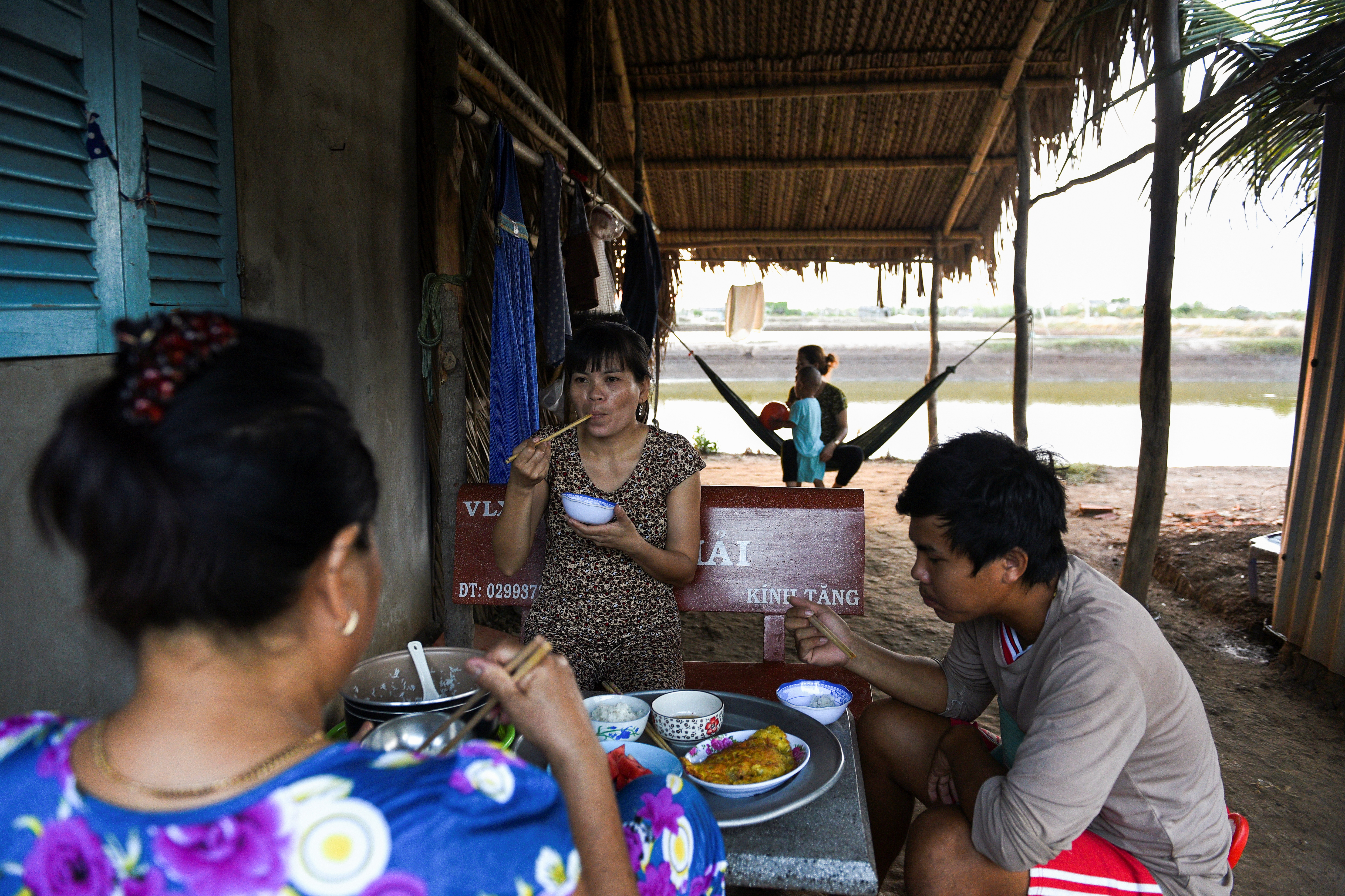 Relatives of a shrimp farmer Ta Thi Thanh Thuy eat dinner at her house in Soc Trang province, Vietnam, May 1, 2021. Picture taken May 1, 2021. REUTERS/Thanh Hue