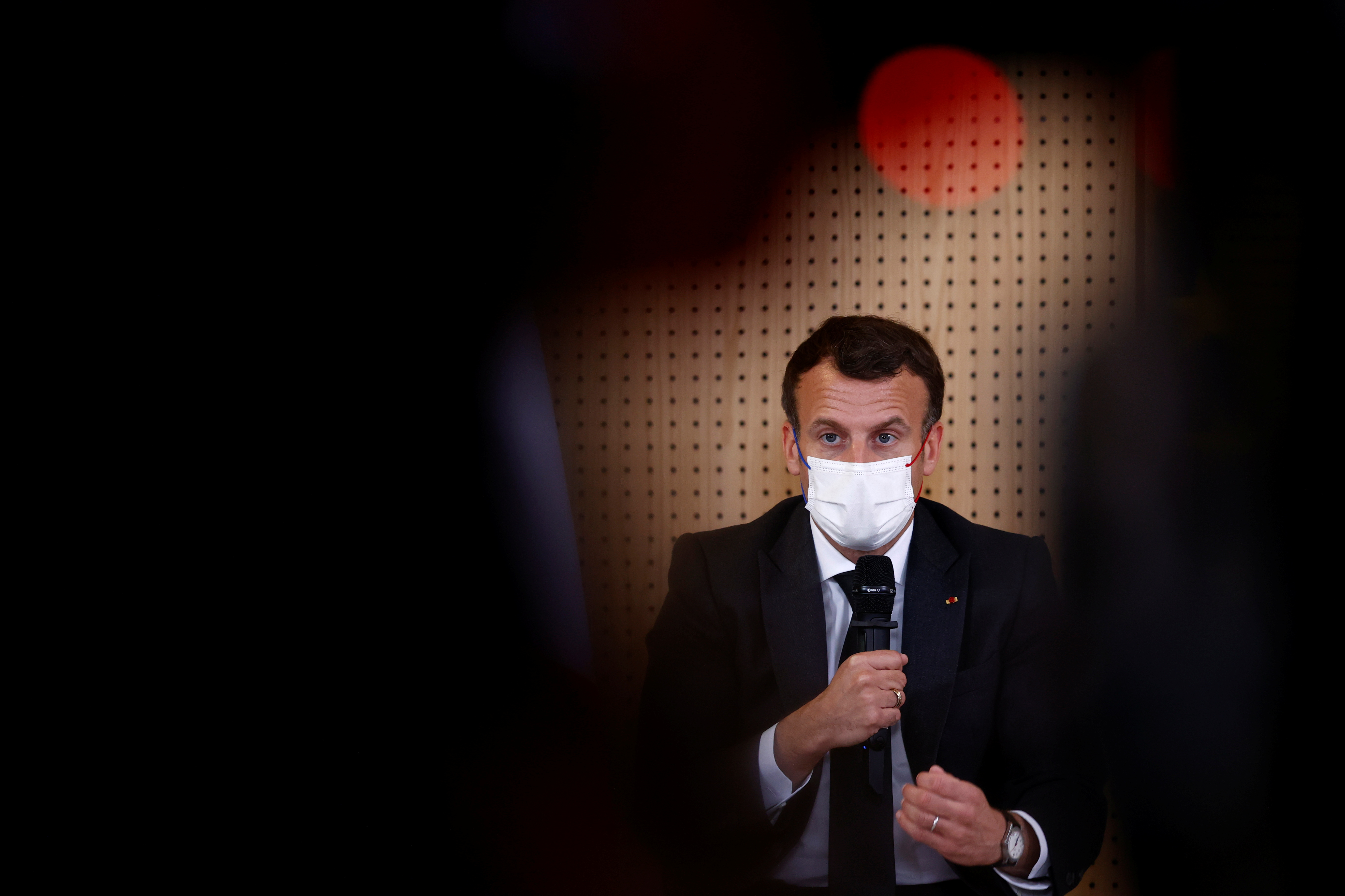 French President Emmanuel Macron, wearing a protective face mask, talks during a meeting with medical staff members during a visit in a child psychiatry department at Reims hospital. April 14, 2021.  REUTERS/Christian Hartmann/Pool
