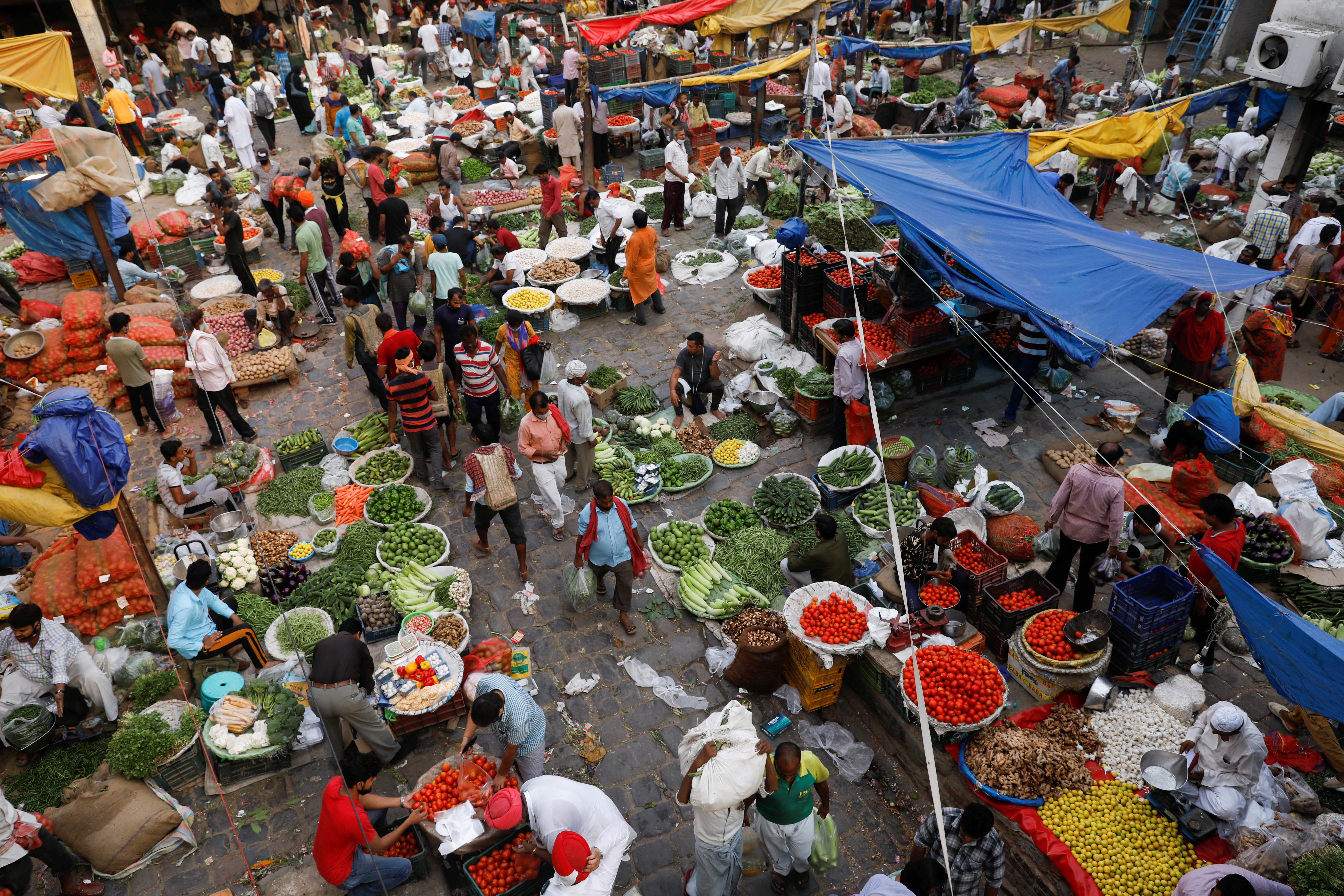 People shop at a crowded wholesale vegetable market after authorities eased coronavirus restrictions, following a drop in COVID-19 cases, in the old quarters of Delhi, India, June 23, 2021. REUTERS/Adnan Abidi/File Photo