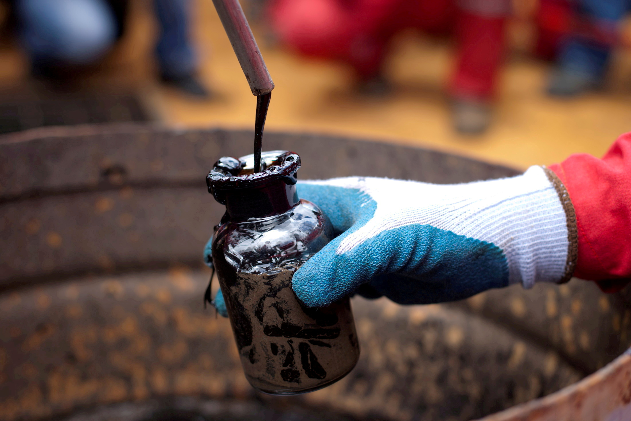 A worker collects a crude oil sample at an oil well operated by Venezuela's state oil company PDVSA in Morichal, Venezuela, July 28, 2011.  REUTERS/Carlos Garcia Rawlins/File Photo