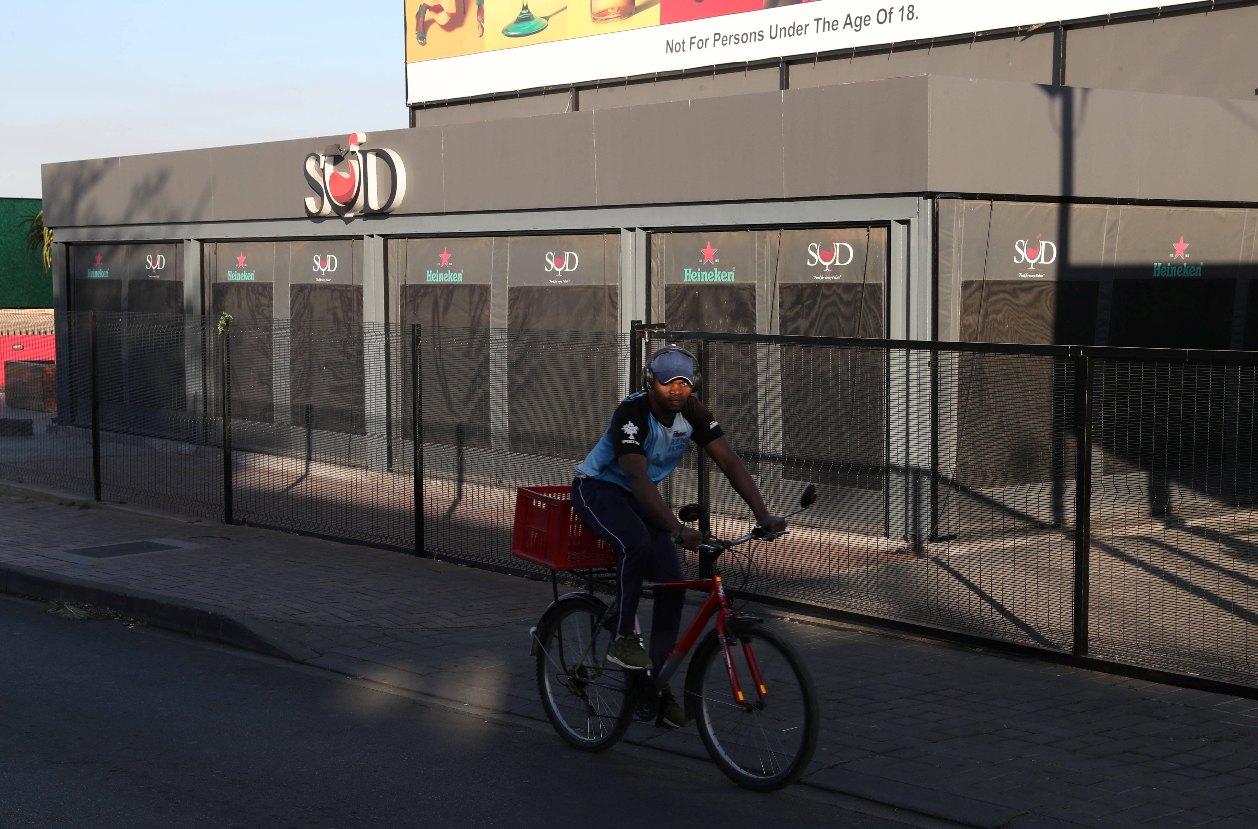 A man cycles past a restaurant closed during the coronavirus disease (COVID-19) outbreak as the country faces tougher lockdown restrictions in Soweto, South Africa, June 28, 2021. REUTERS/Siphiwe Sibeko