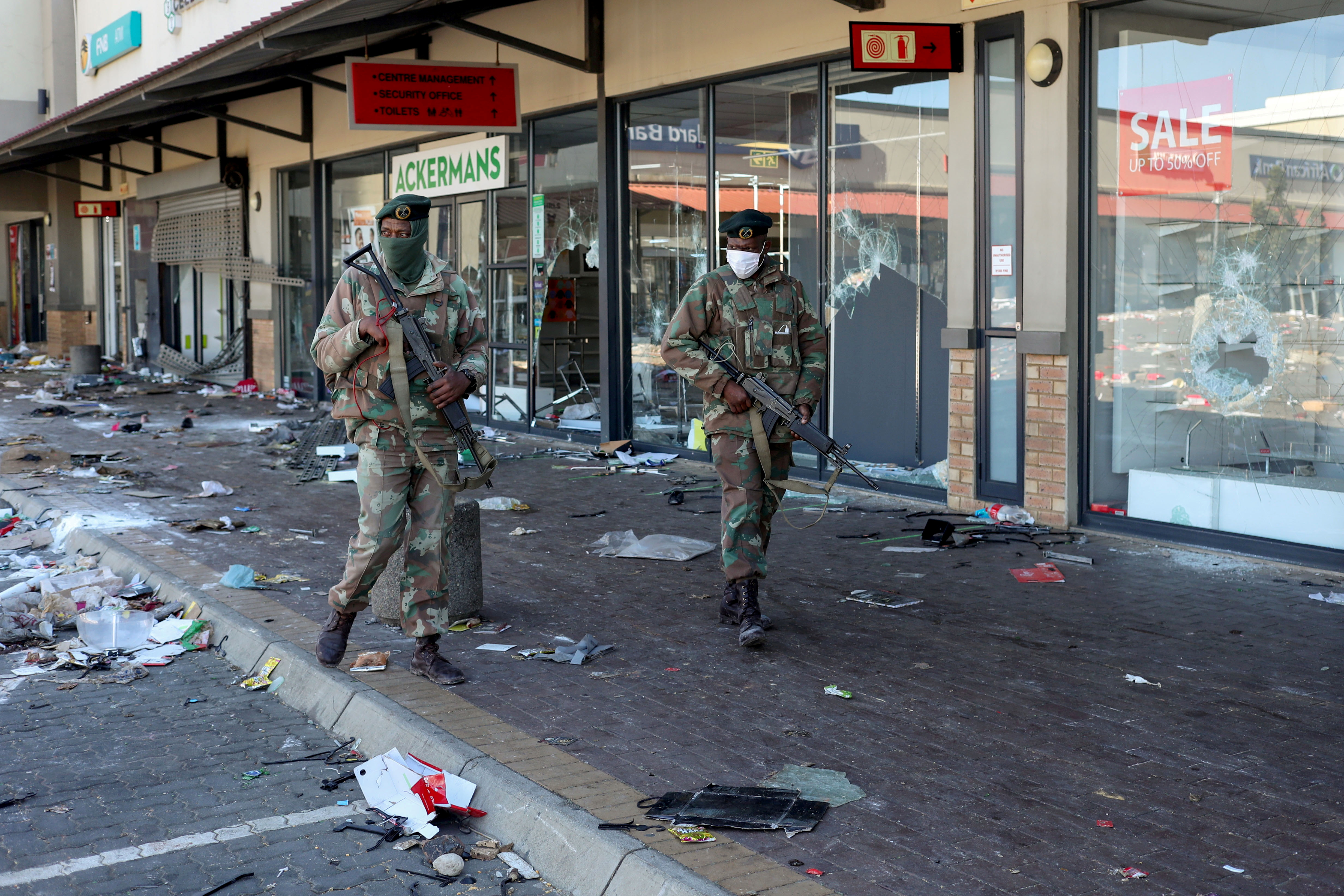 Members of the military patrol past looted shops as the country deploys army to quell unrest linked to jailing of former President Jacob Zuma, in Soweto, South Africa, July 13, 2021. REUTERS/Siphiwe Sibeko     TPX IMAGES OF THE DAY
