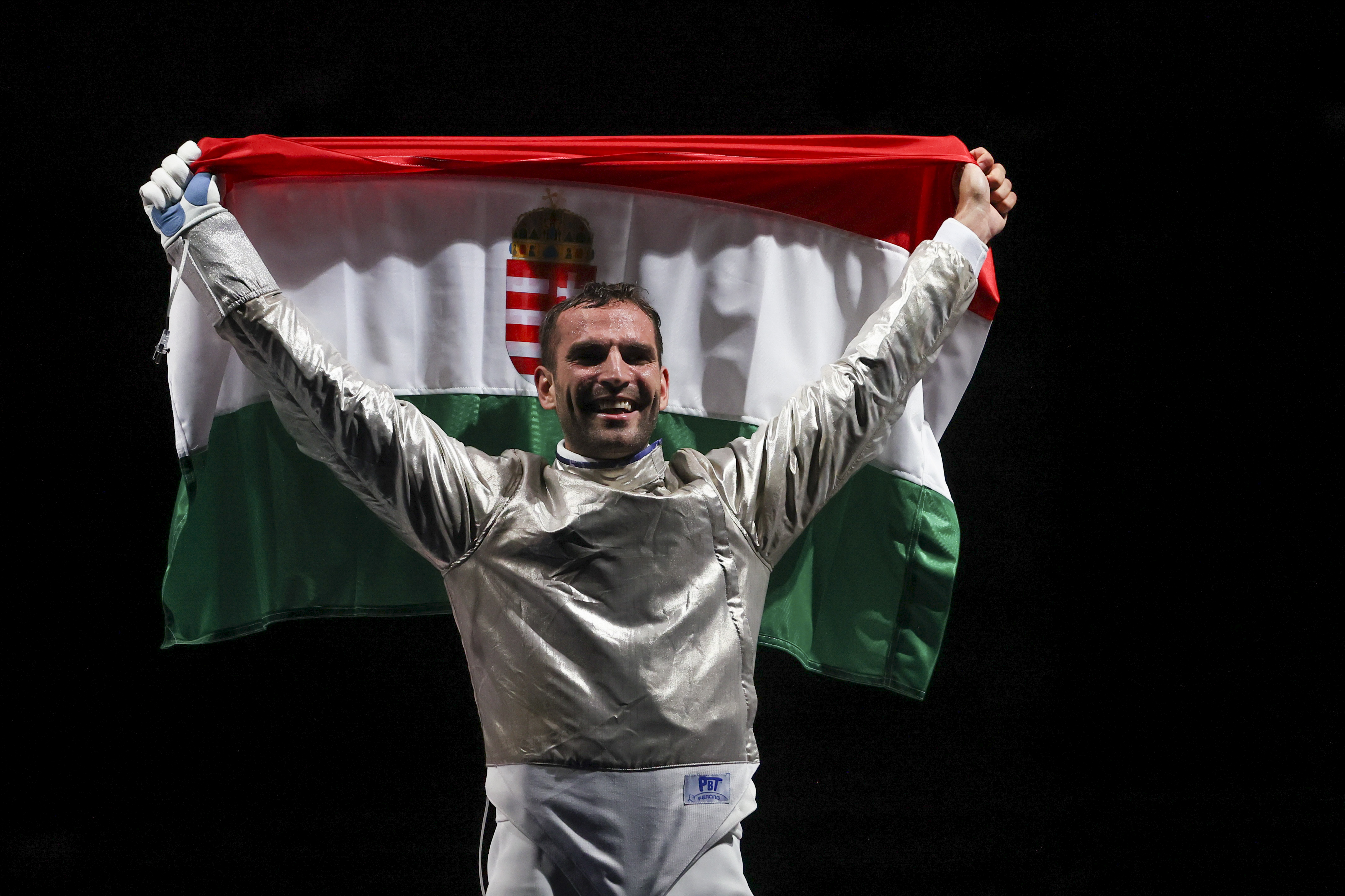 Tokyo 2020 Olympics - Fencing - Men's Individual Sabre - Gold medal match - Makuhari Messe Hall B - Chiba, Japan - July 24, 2021. Aron Szilagyi of Hungary celebrates after winning gold as he holds the flag of Hungary REUTERS/Maxim Shemetov