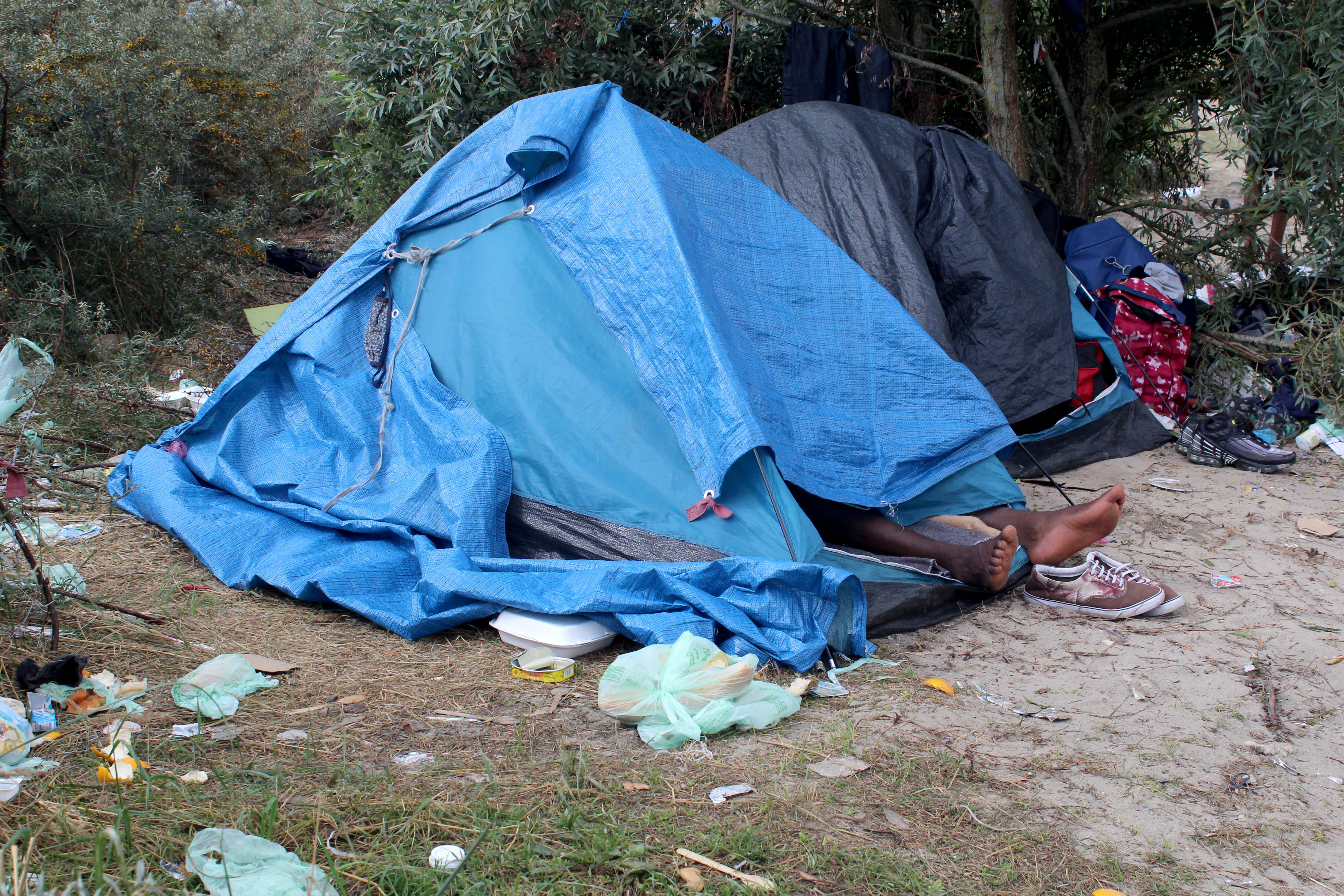 A migrant sleeps in tent at a makeshift migrant camp near the hospital in Calais, France, September 10, 2021. REUTERS/Forrest Crellin