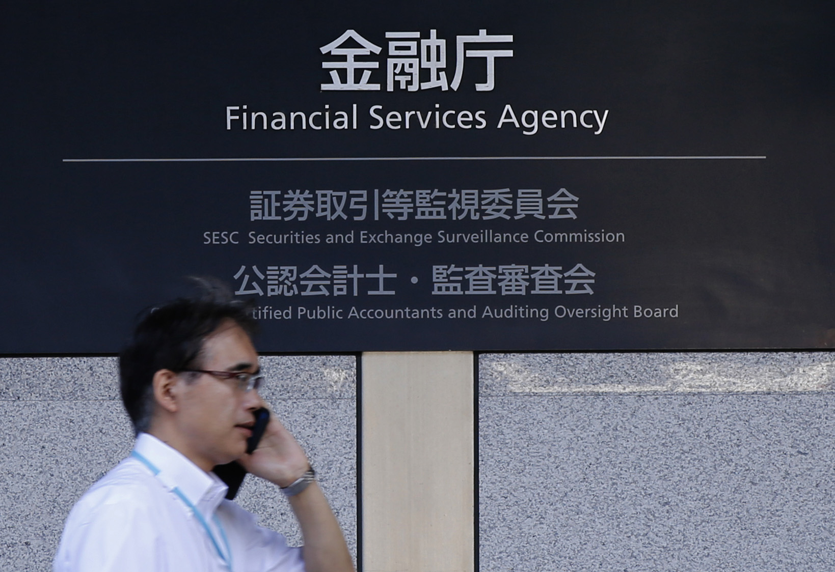 A man walks past a sign of Japan's Financial Services Agency in Tokyo August 7, 2014.  REUTERS/Toru Hanai