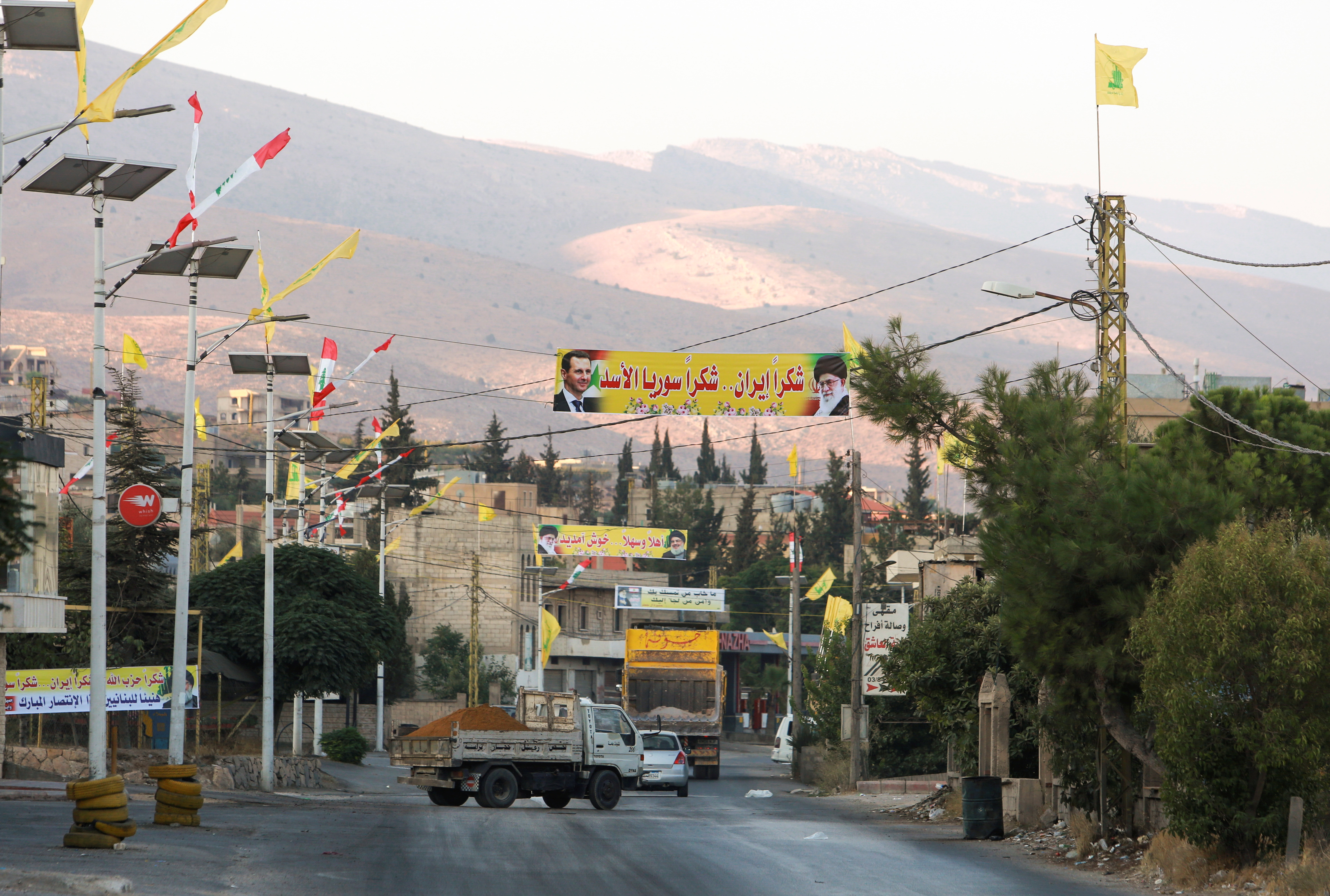 Vehicles ride near a banner depicting Syria's President Bashar al-Assad, and Iran's Supreme Leader Ayatollah Ali Khamenei as the first truck carrying Iranian fuel is expected to reach Lebanon today, near the Lebanese-Syrian border, in al-Ain village, Lebanon September 16, 2021. REUTERS/Aziz Taher