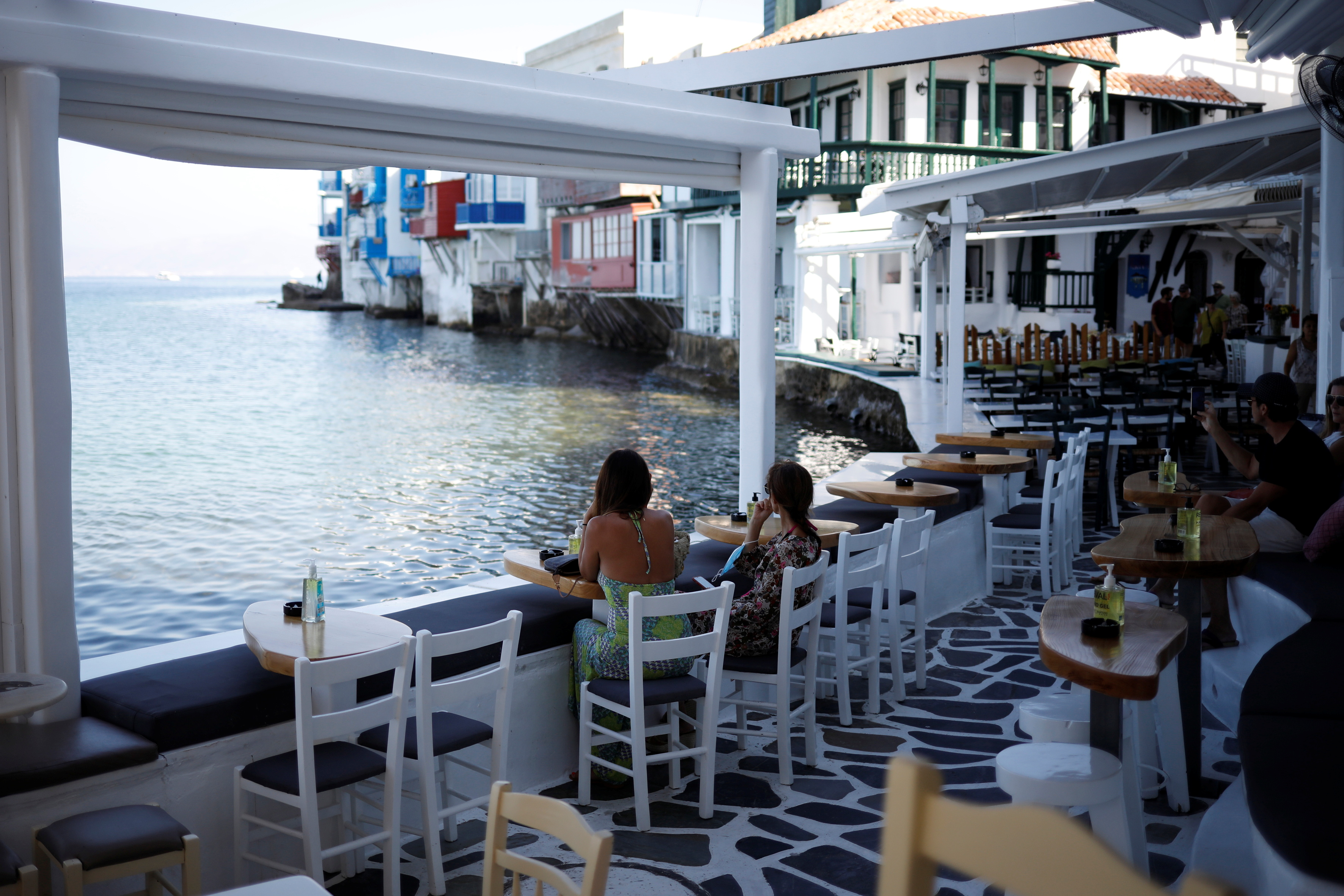 People enjoy the view in a cafe in Little Venice as Greece banned music in restaurants and bars and imposed a nighttime curfew on the island of Mykonos, Greece, July 18, 2021. REUTERS/Louiza Vradi
