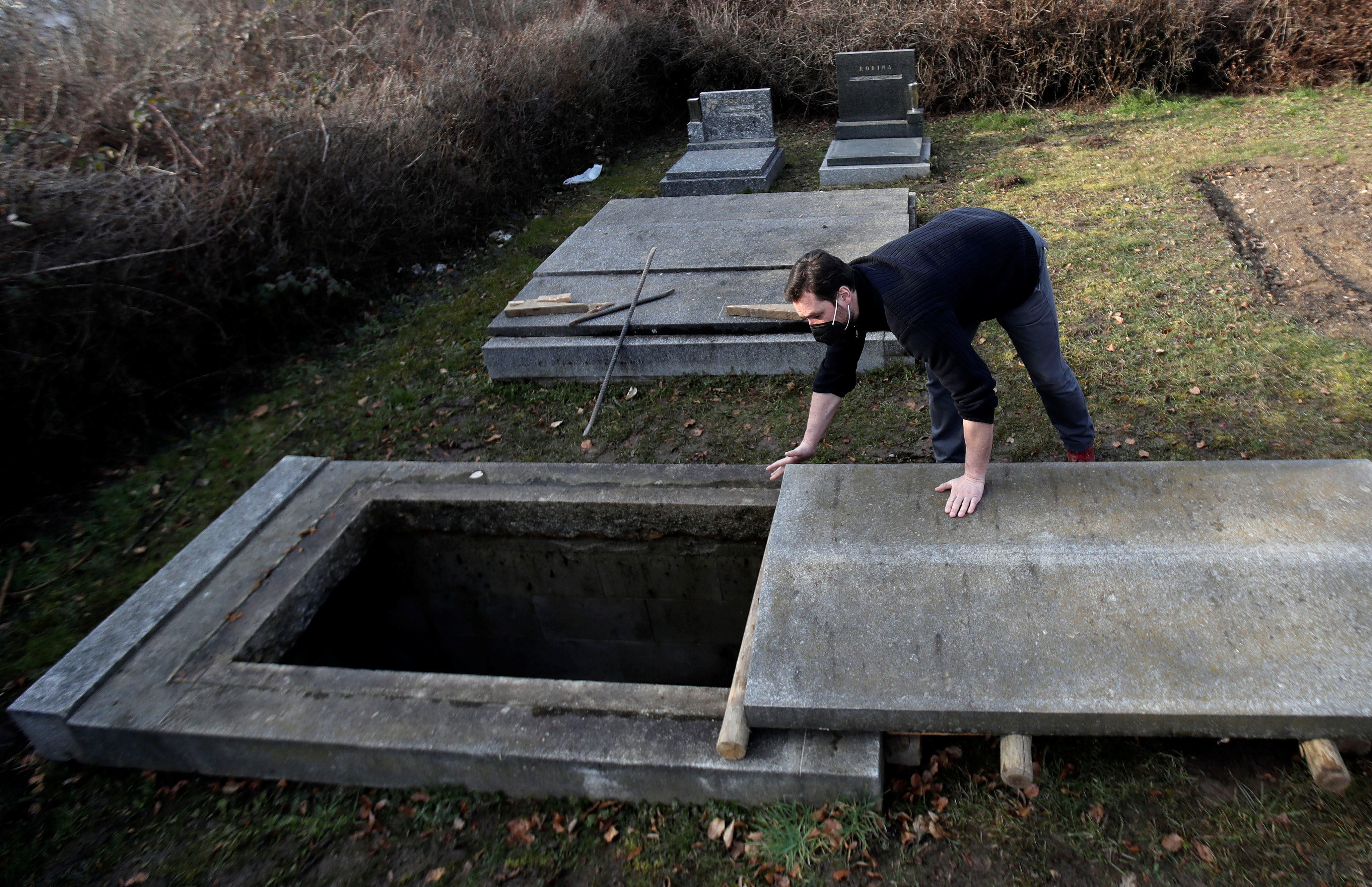 An actor Tomas Novotny opens an empty grave at a training cemetery as a part of his re-qualification procedure amid the coronavirus disease (COVID-19) outbreak in Prague, Czech Republic, March 9, 2021. Picture taken March 9, 2021.   REUTERS/David W Cerny
