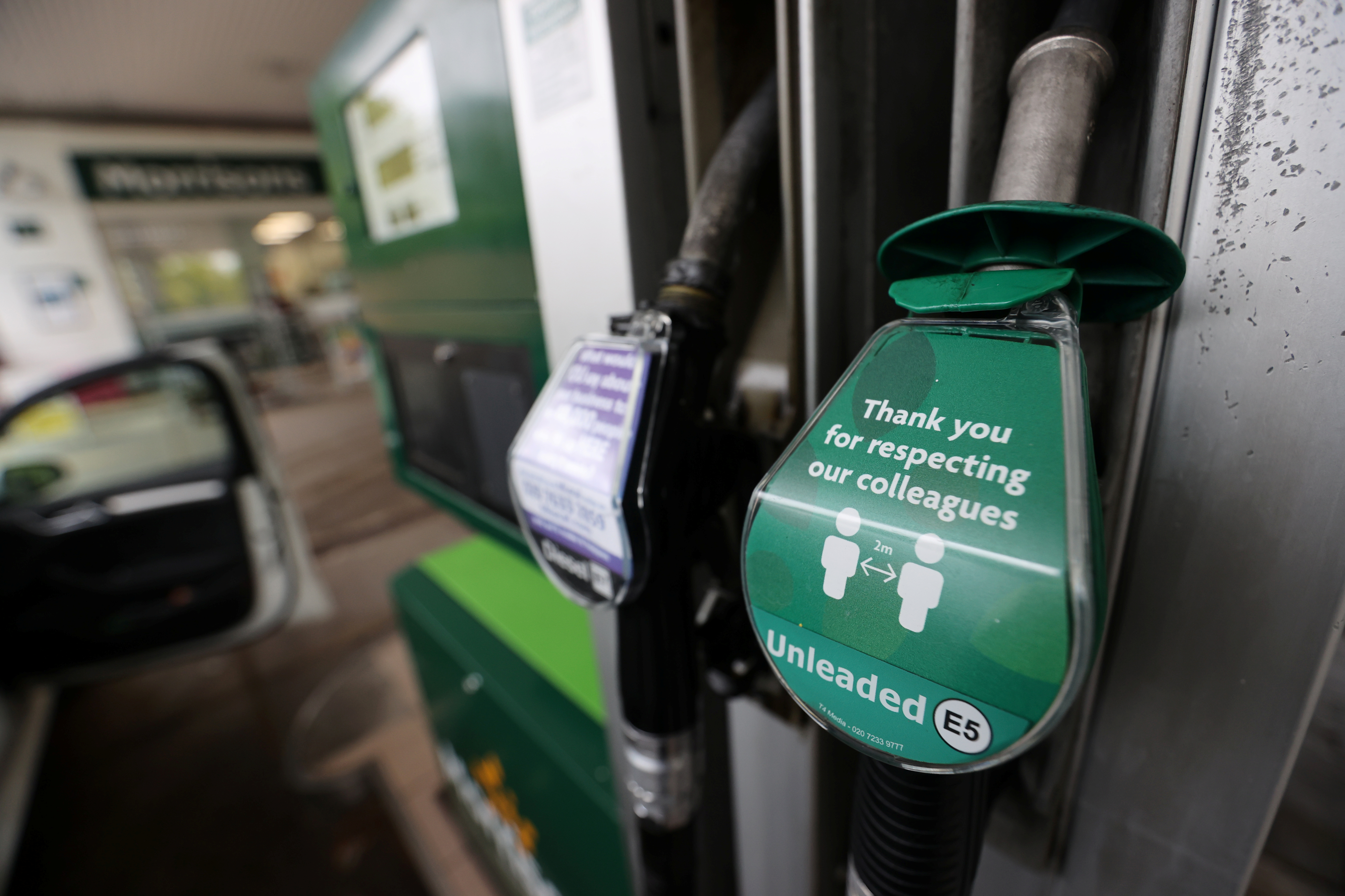 A notice telling people to stay 2 metres apart is seen at a petrol station, following the outbreak of the coronavirus disease (COVID-19), Stone, Britain, April 28, 2020. REUTERS/Carl Recine