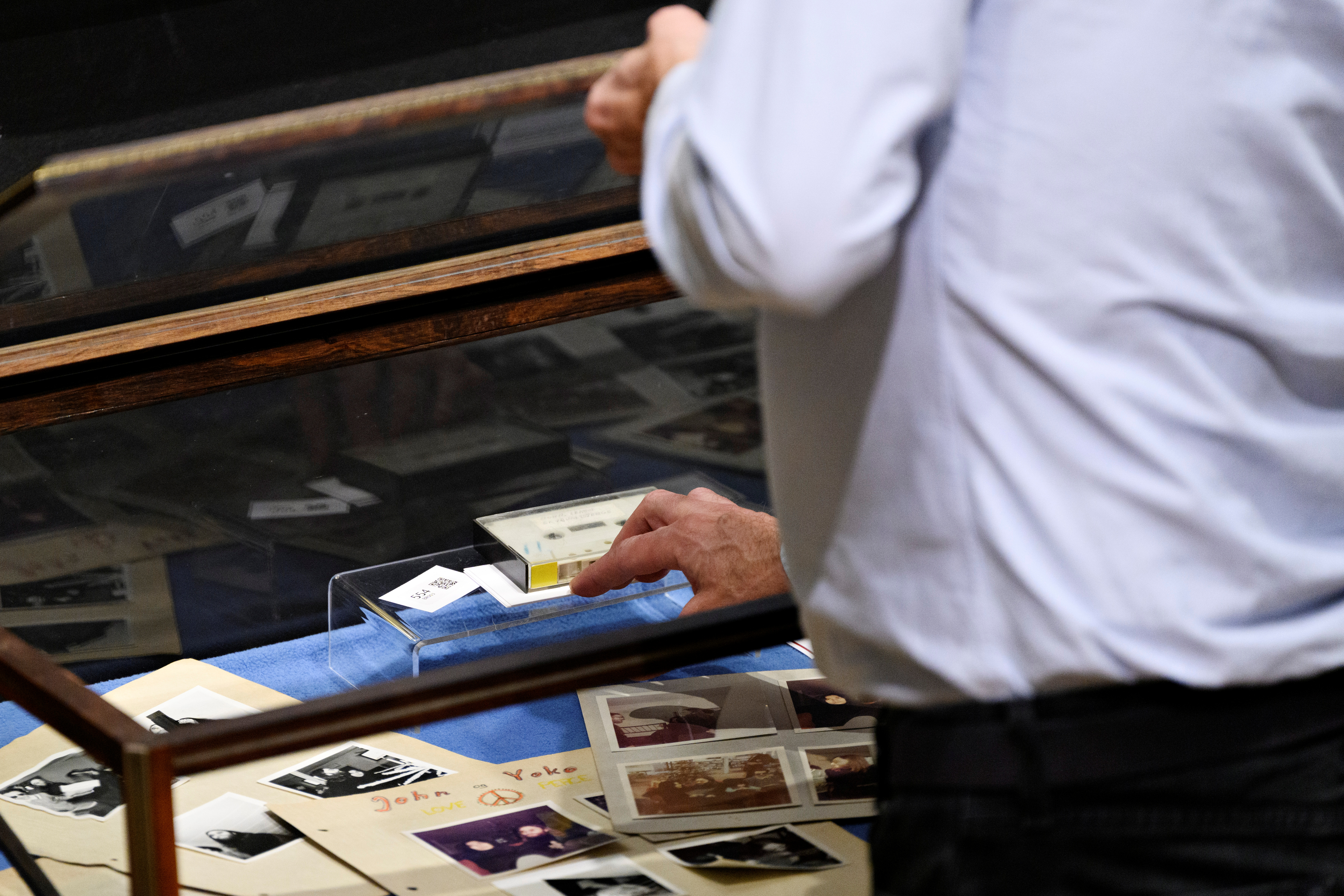 A staff member tends to the items at an auction of polariods and a cassette with the recording of Danish schoolboys' interviews with John Lennon and Yoko Ono during the couple's winter stay in Thy, Jutland, Denmark in 1970 at Bruun Rasmussen Auction House in Copenhagen, Denmark, September 28, 2021. Ritzau Scanpix/Philip Davali via REUTERS