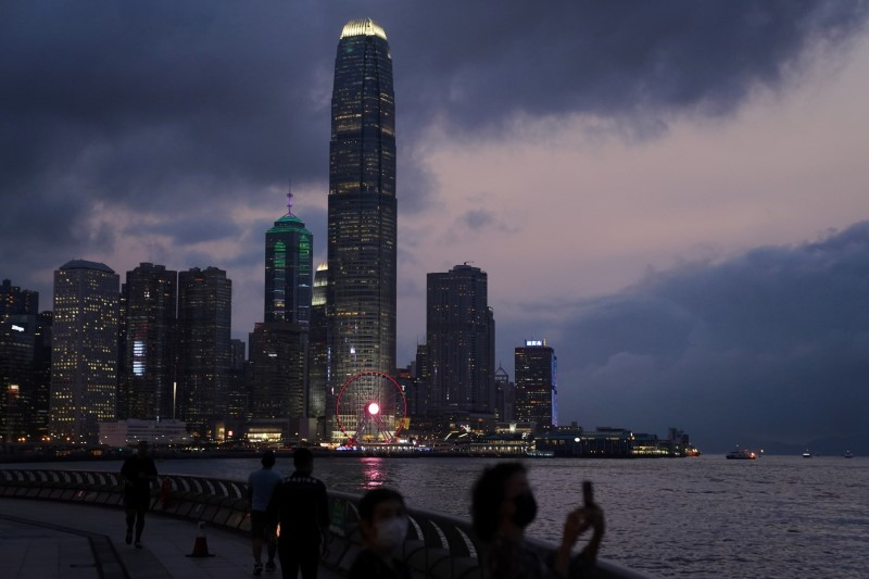 A woman takes pictures in front of high-rise buildings in the Central financial district after sunset in Hong Kong, China March 30, 2021. REUTERS/Lam Yik - RC2NLM99HBBA