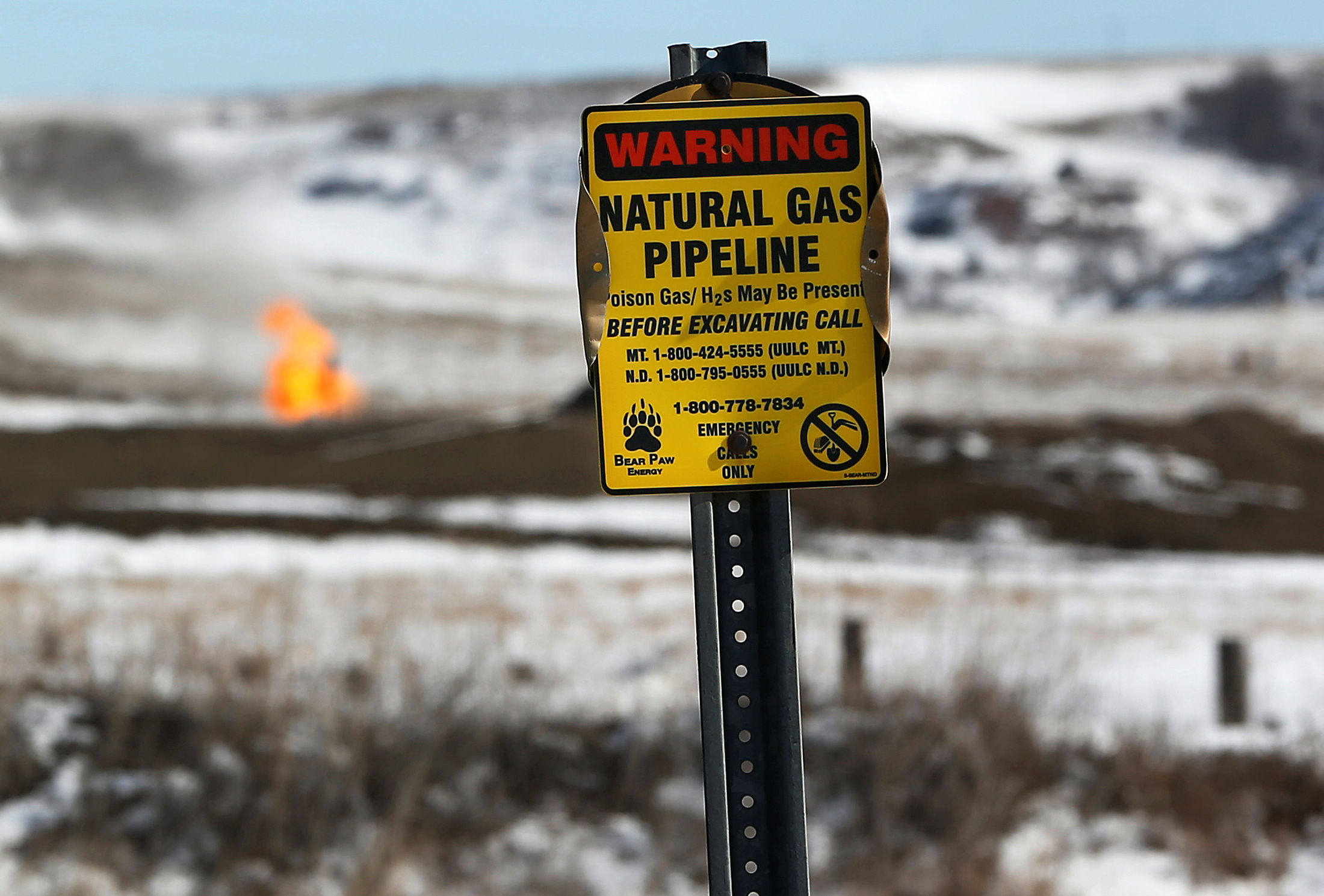 A warning sign for a natural gas pipeline is seen in front of natural gas flares at an oil pump site outside of Williston, North Dakota March 11, 2013.  REUTERS/Shannon Stapleton/