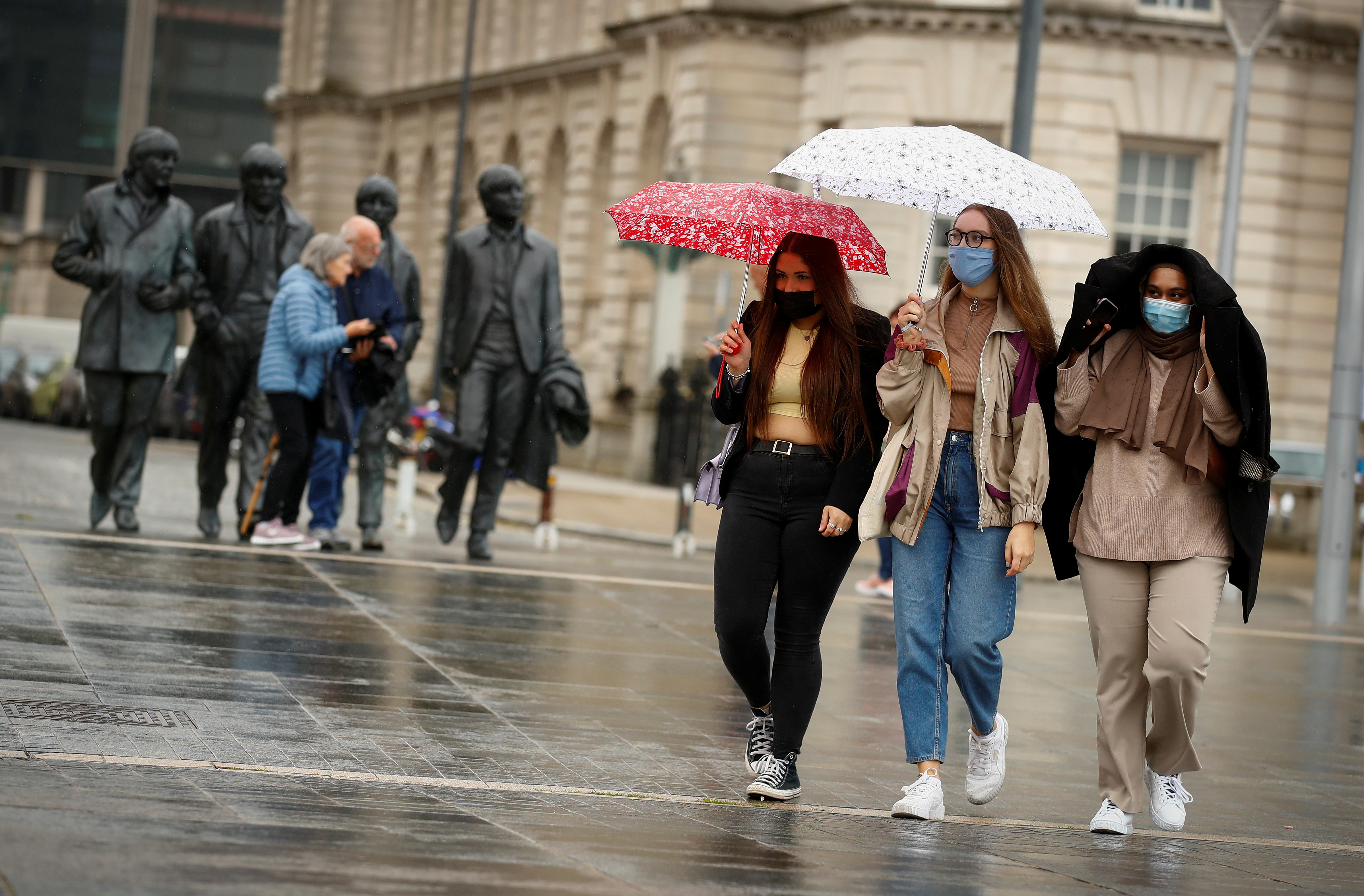 Students Sophie Langford, Emily Campbell and Tamzida Begun walk to the mass vaccine centre at Liverpool Pier Head that is offering walk in visits for the coronavirus (COVID-19) vaccine in Liverpool, Britain, June 23, 2021.  REUTERS/Jason Cairnduff