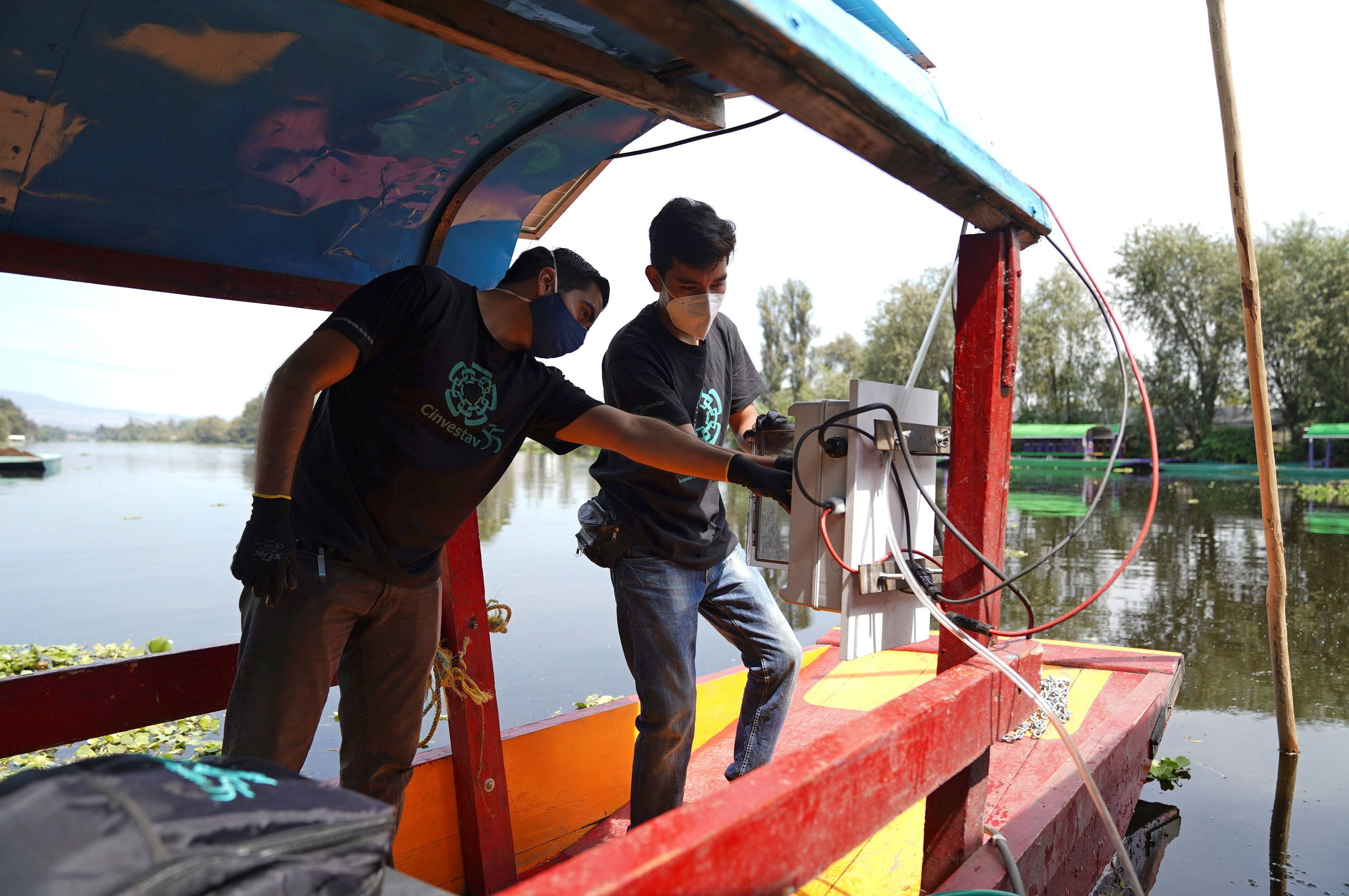 """Members of a team of researchers from the Center for Research and Advanced Studies (Cinvestav), who developed a method that converts solar energy into photovoltaic energy that activates a pump that sends """"nanobubbles"""" into the water, install a pump in a trajinera boat as part of a project to clean the polluted waters at the canals of Xochimilco, in Mexico City, Mexico August 20, 2021. REUTERS/Toya Sarno Jordan"""