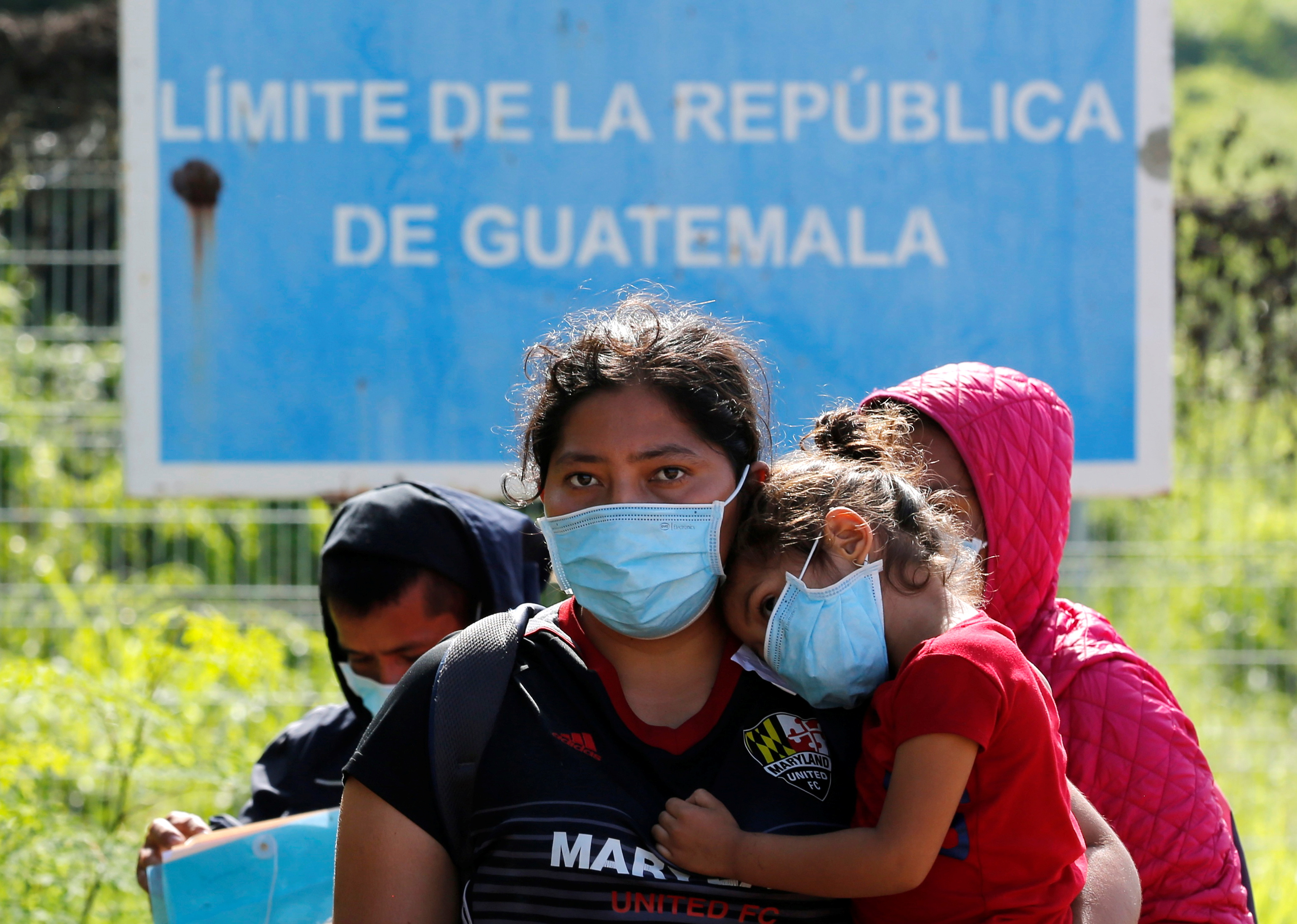 Central American migrants stand at the Mexico - Guatemala border after they were expelled by U.S. and Mexican officials, in El Ceibo, Guatemala August 15, 2021. The sign reads