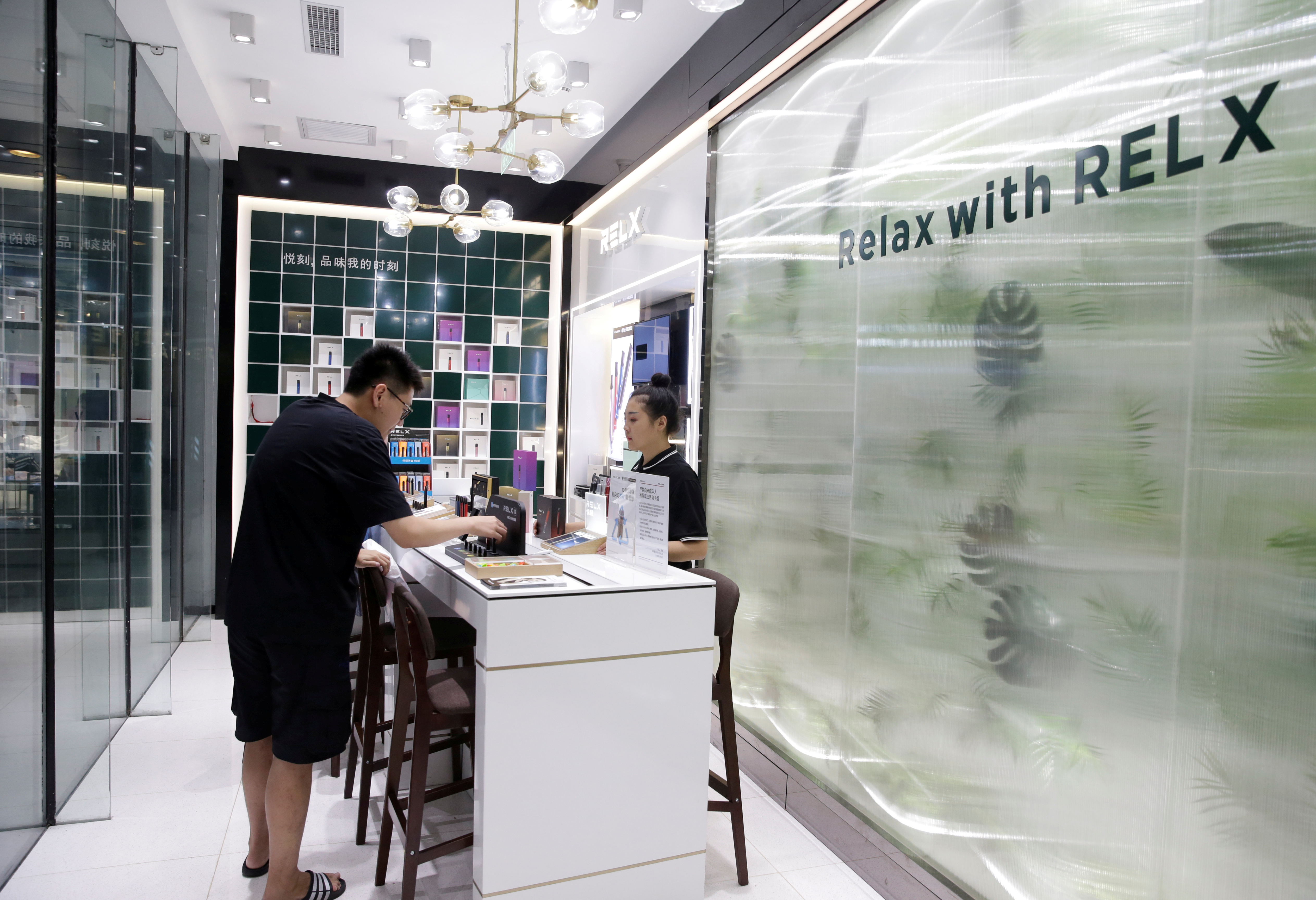 A customer selects Relx e-cigarettes at its flagship store in Beijing, China, August 2, 2019. REUTERS/Jason Lee/File Photo