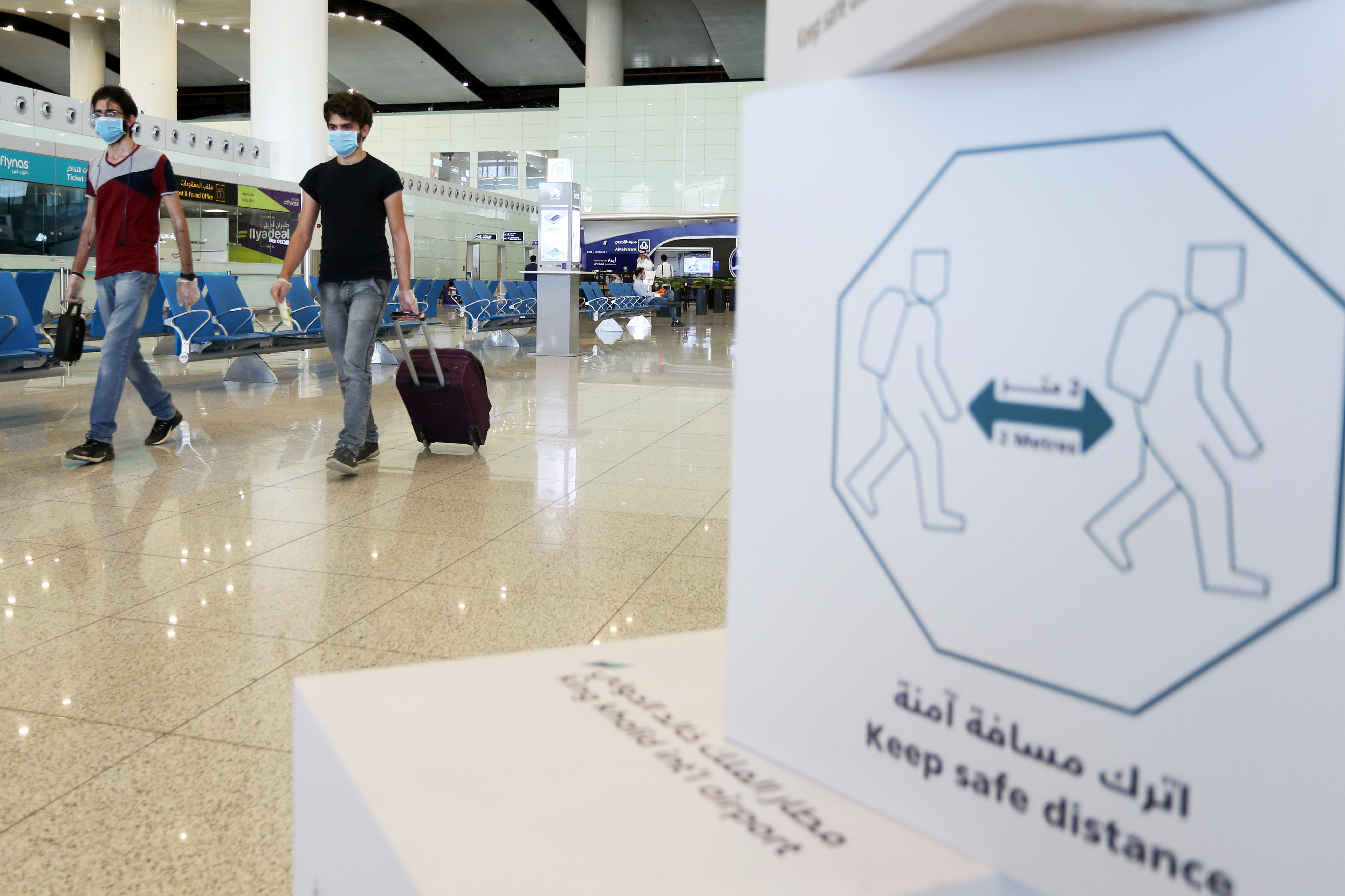 Travellers wearing protective face masks walk at Riyadh International Airport, after Saudi Arabia reopened domestic flights, following the outbreak of the coronavirus disease (COVID-19), in Riyadh, Saudi Arabia May 31, 2020. REUTERS/Ahmed Yosri