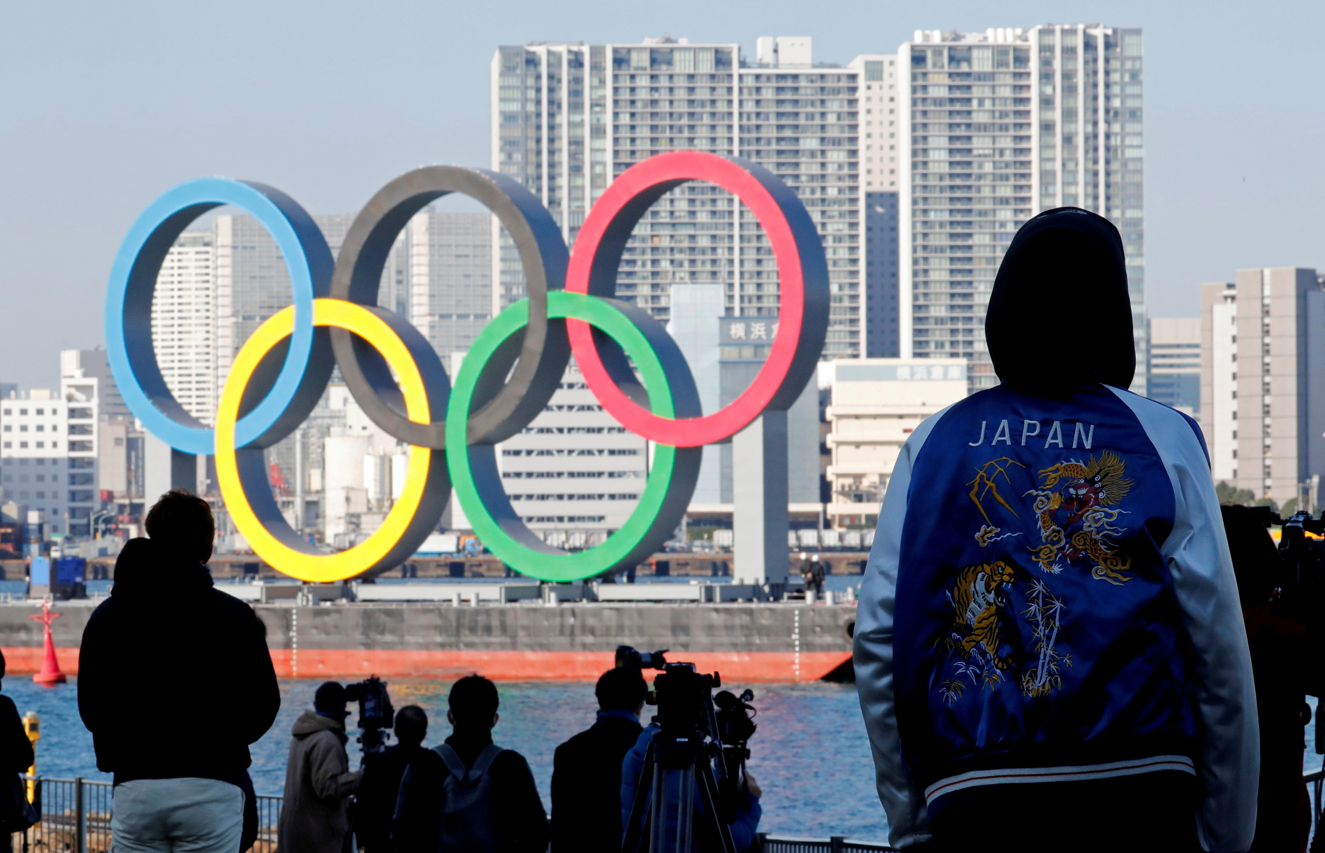 Bystanders watch as giant Olympic rings are reinstalled at the waterfront area at Odaiba Marine Park, after they were temporarily taken down in August for maintenance amid the coronavirus disease (COVID-19) outbreak, in Tokyo, Japan December 1, 2020. REUTERS/Kim Kyung-Hoon/File Picture