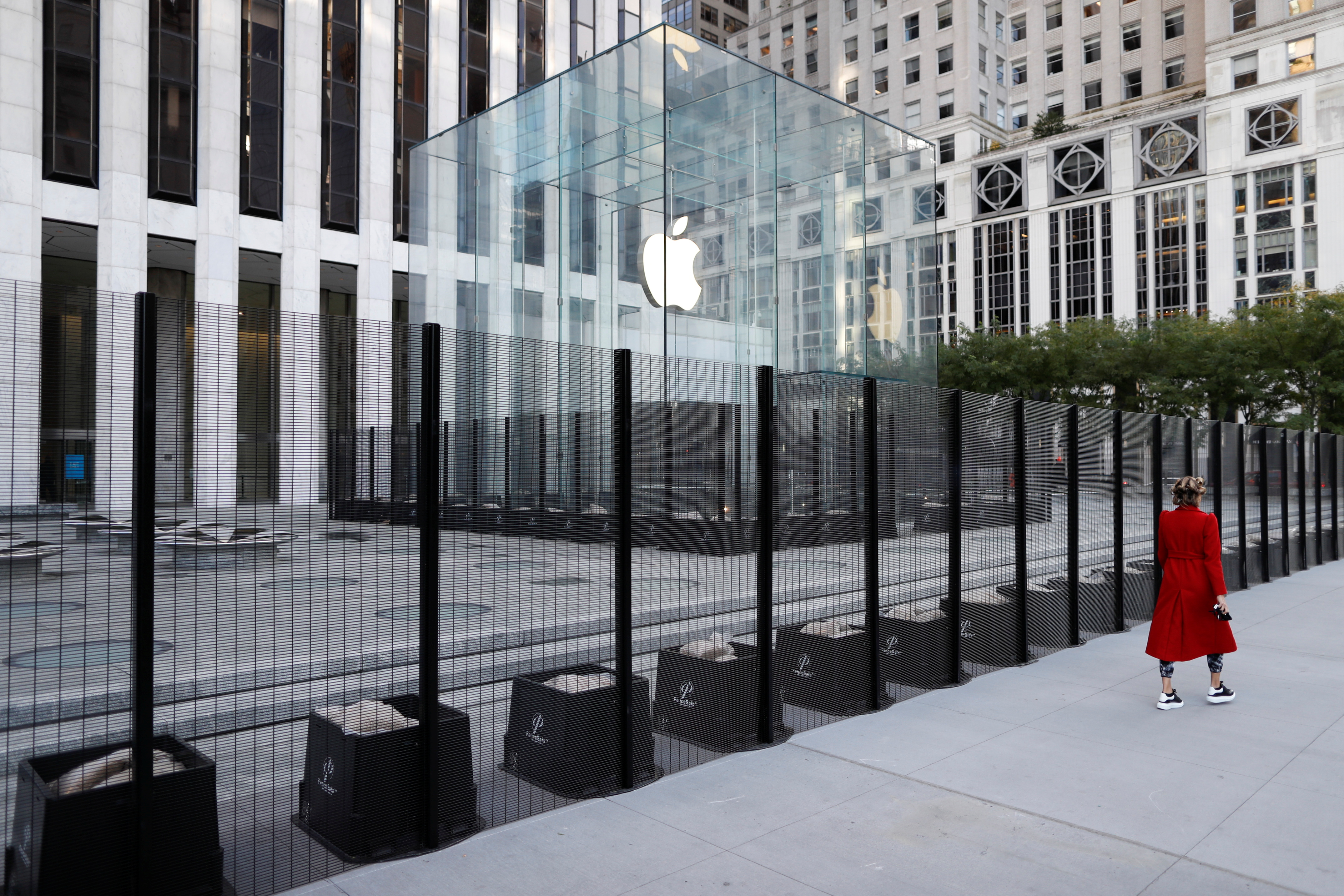 A person walks past a security fence erected around the Apple Fifth Avenue store as votes continue to be counted following the 2020 U.S. presidential election, in Manhattan, New York City, U.S., November 5, 2020. REUTERS/Andrew Kelly