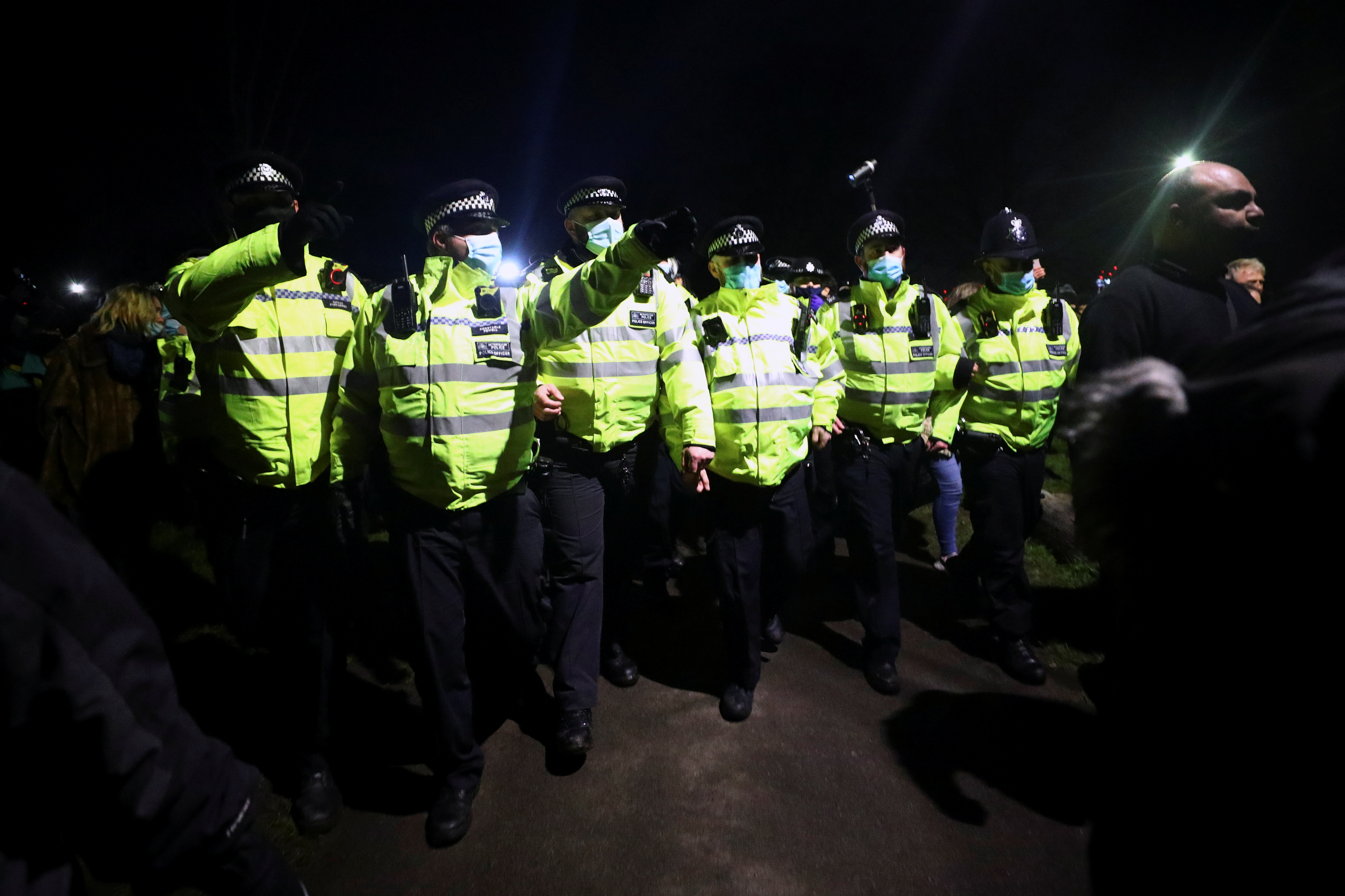 Police members gesture as people gather at a memorial site in Clapham Common Bandstand, following the kidnap and murder of Sarah Everard, in London, Britain March 13, 2021. REUTERS/Hannah McKay