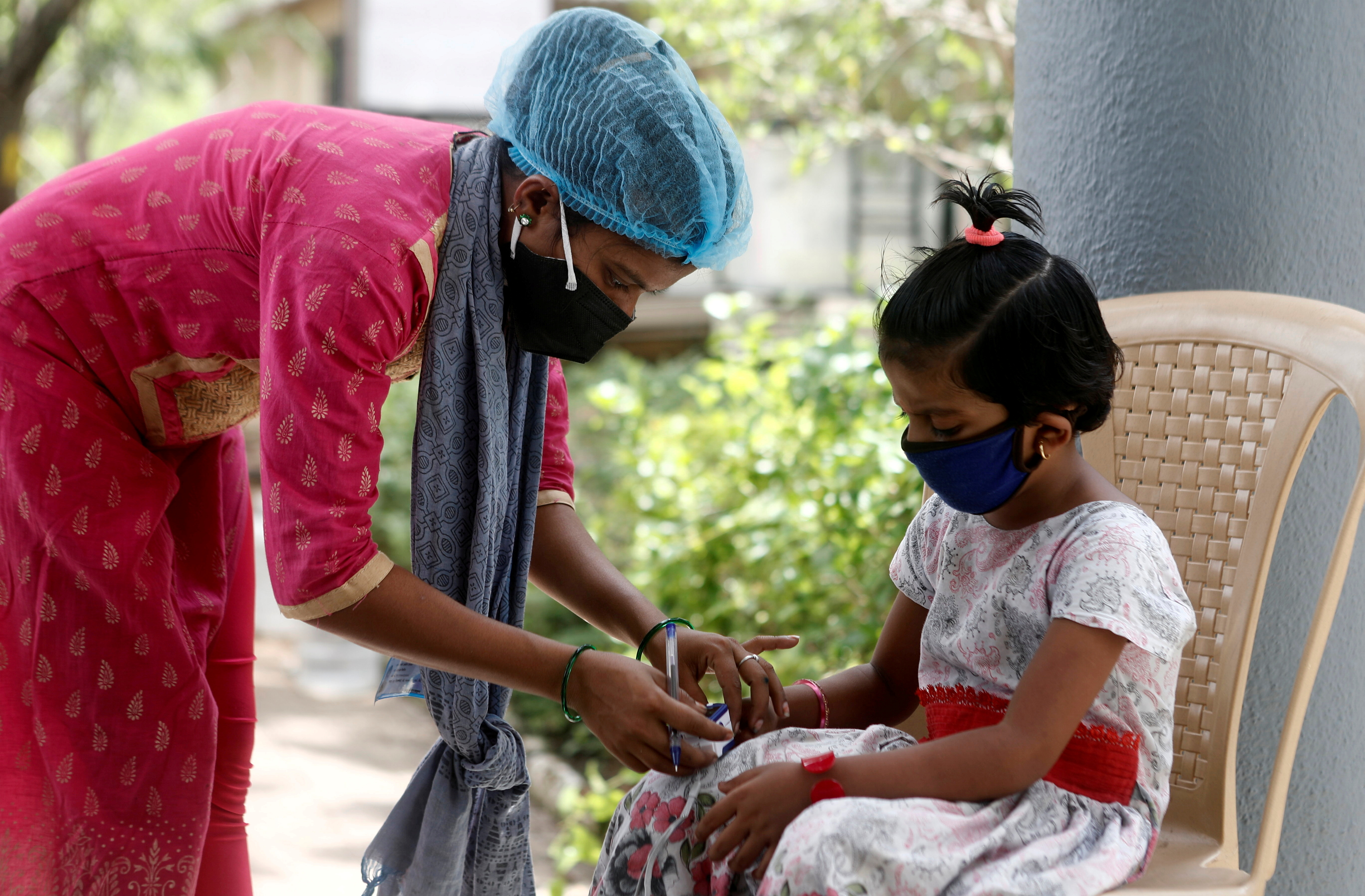 A nurse checks a coronavirus disease patient's pulse before she is admitted into a school turned COVID-19 care facility on the outskirts of Mumbai, India, May 24, 2021. REUTERS/Francis Mascarenhas/File Photo